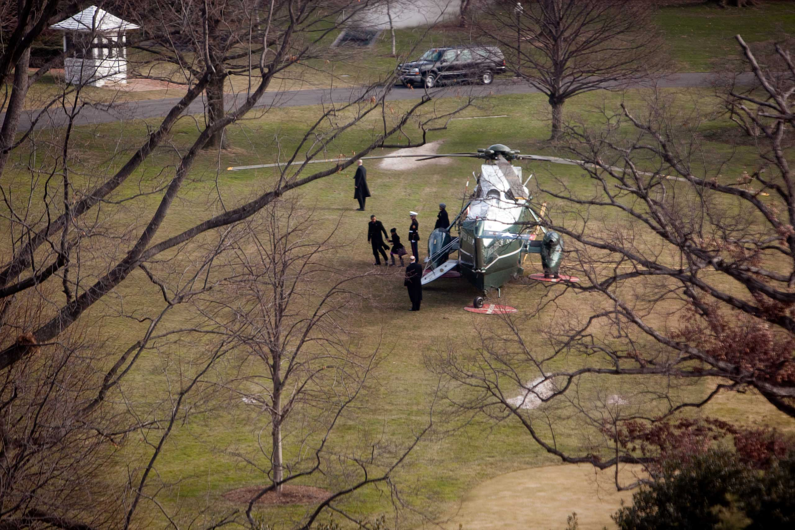 President Barack Obama holds hands with daughter Sasha as they walk away from Marine One on the South Lawn of the White House in Washington D.C. after arriving home from their vacation in Hawaii, with Clancy facing outward nearby, on Jan. 4, 2010.