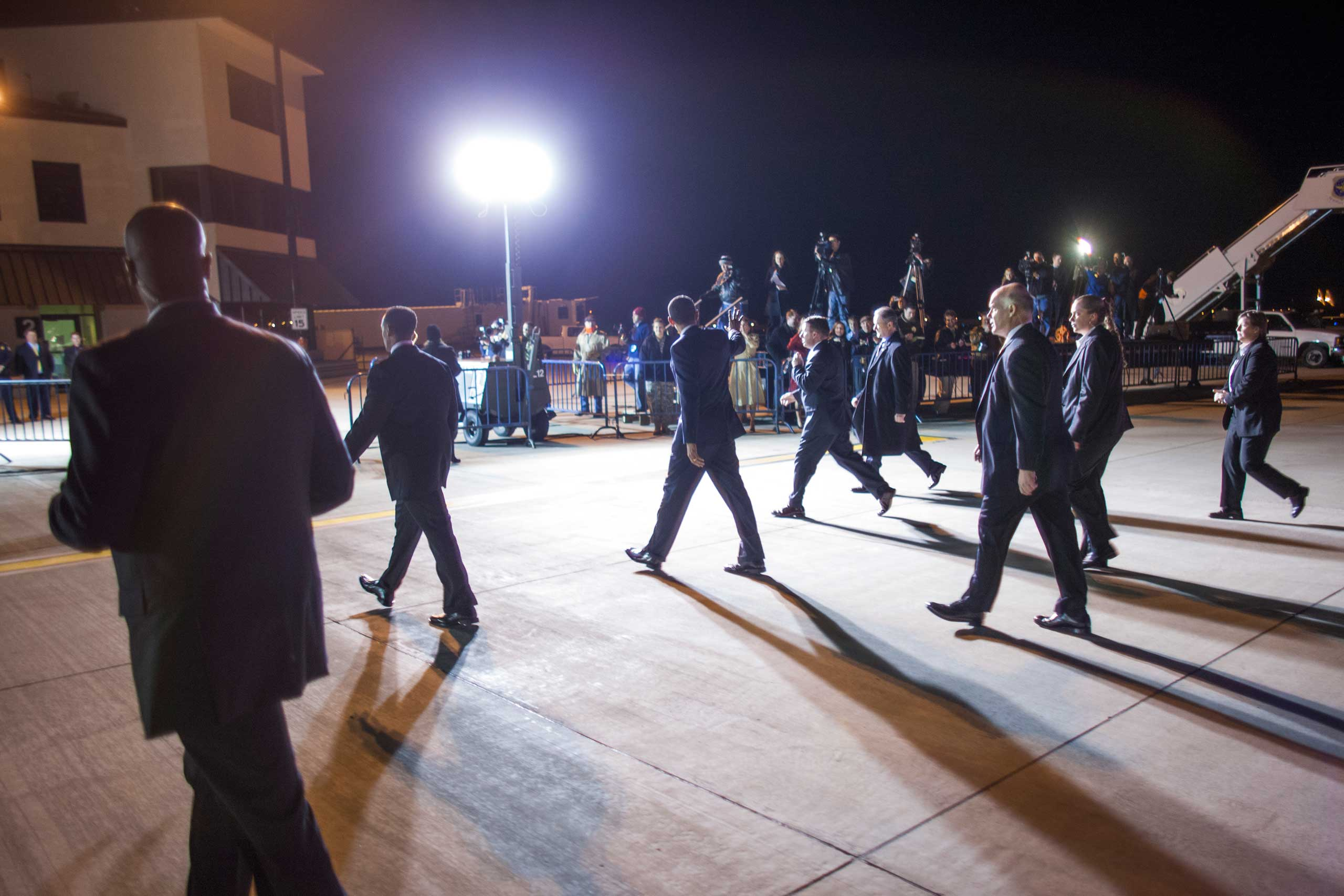 A flood of bright lights fall on Clancy and other agents as the President waves to press watching the arrival of Air Force One in Springfield, Ill. on Feb. 12, 2009.