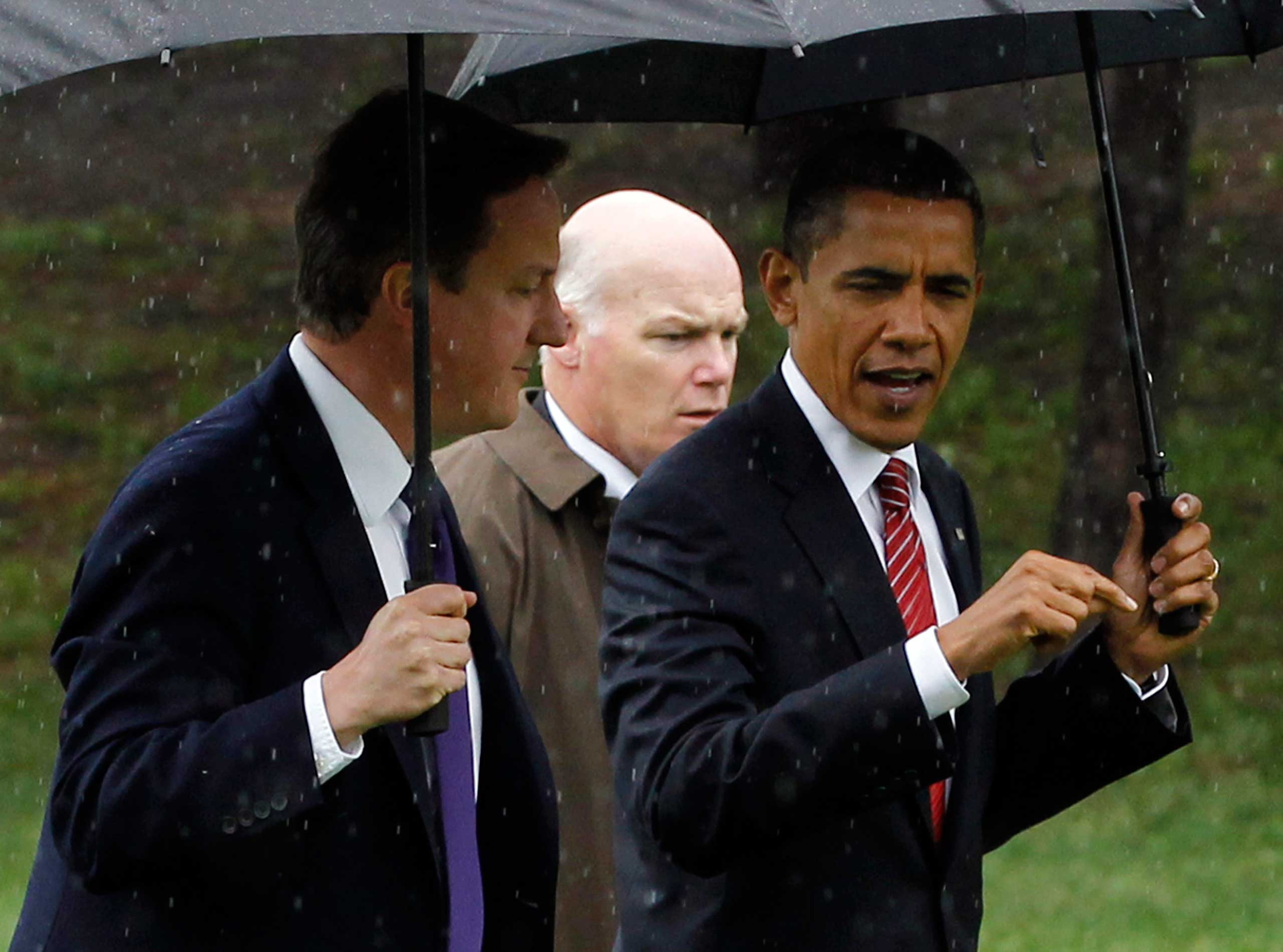 Clancy braves the rain as umbrella-carrying President Barack Obama and British Prime Minister David Cameron walk from Marine One in Toronto, after their flight from the G8 Summit to the G20 Summit on June 26, 2010.