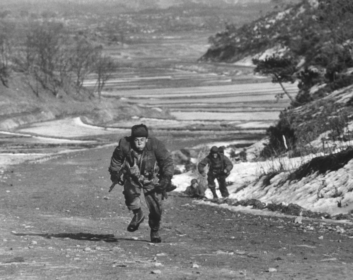 A rifleman dashes uphill to take cover from enemy fire, Korea, 1951.