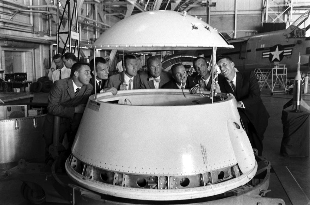 "<b>Not published in LIFE. </b>The original Mercury 7 astronauts (from left: Gus Grissom, Deke Slayton, Gordon Cooper, John Glenn, Scott Carpenter -- the man who spoke the famous and moving words, ""Godspeed, John Glenn,"" during the countdown before Glenn's 1962 orbital flight -- Alan Shepard, and Wally Schirra) inspect an early design of a space program module."
