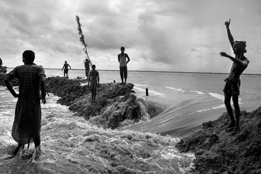 People rest after building dikes to stop the rise of sea water in Ghoramara Island, India
