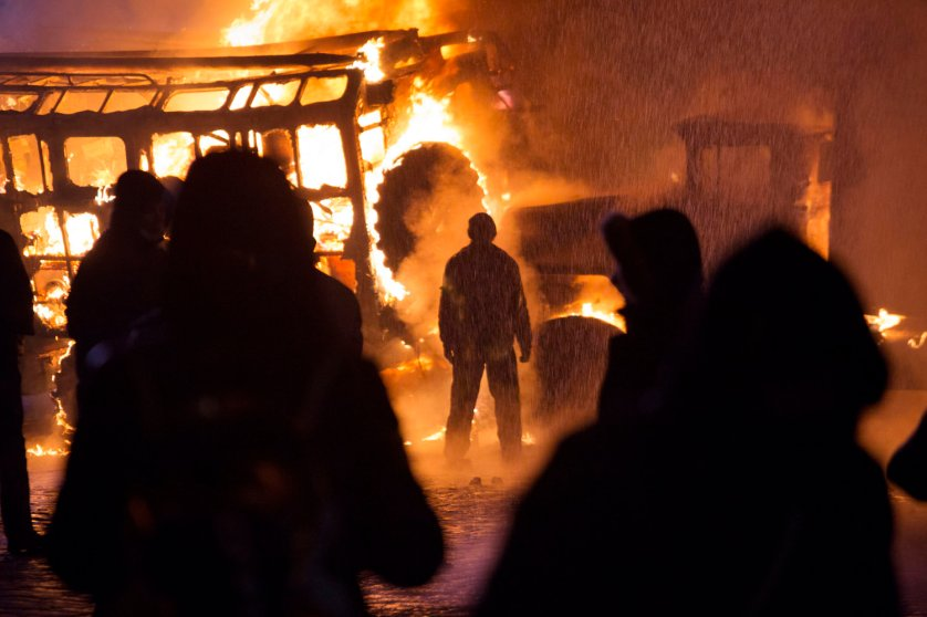 A demonstrator stands in front of burning vehicles during violent clashes with police near Hrushevsky Street, Jan. 19, 2014.