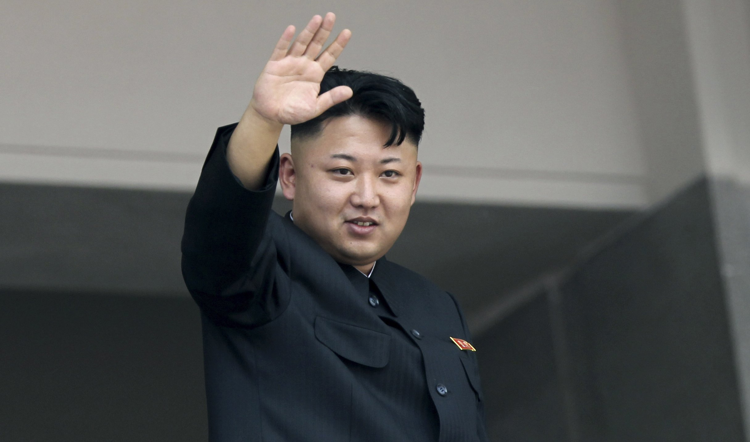 Kim Jong Un waves to spectators and participants of a mass military parade celebrating the 60th anniversary of the Korean War armistice in Pyongyang on July 27, 2013.