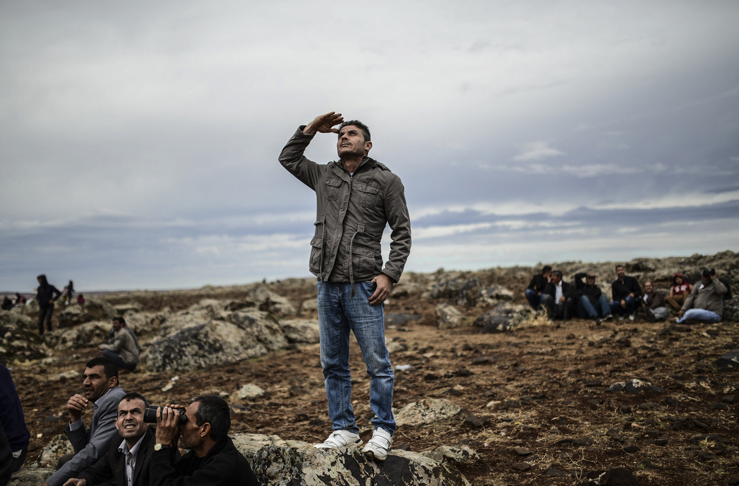 Kurdish people watch jet-fighters fly over Kobani from the Turkish border in the southeastern village of Mursitpinar on October 19, 2014.