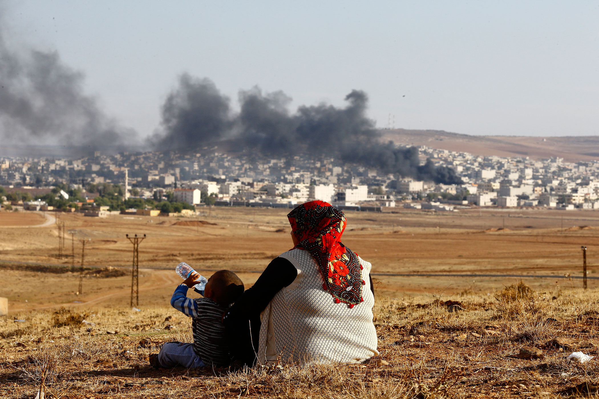 Turkish Kurds watch as smoke rises over the Syrian town of Kobani after an airstrike, October 18, 2014.