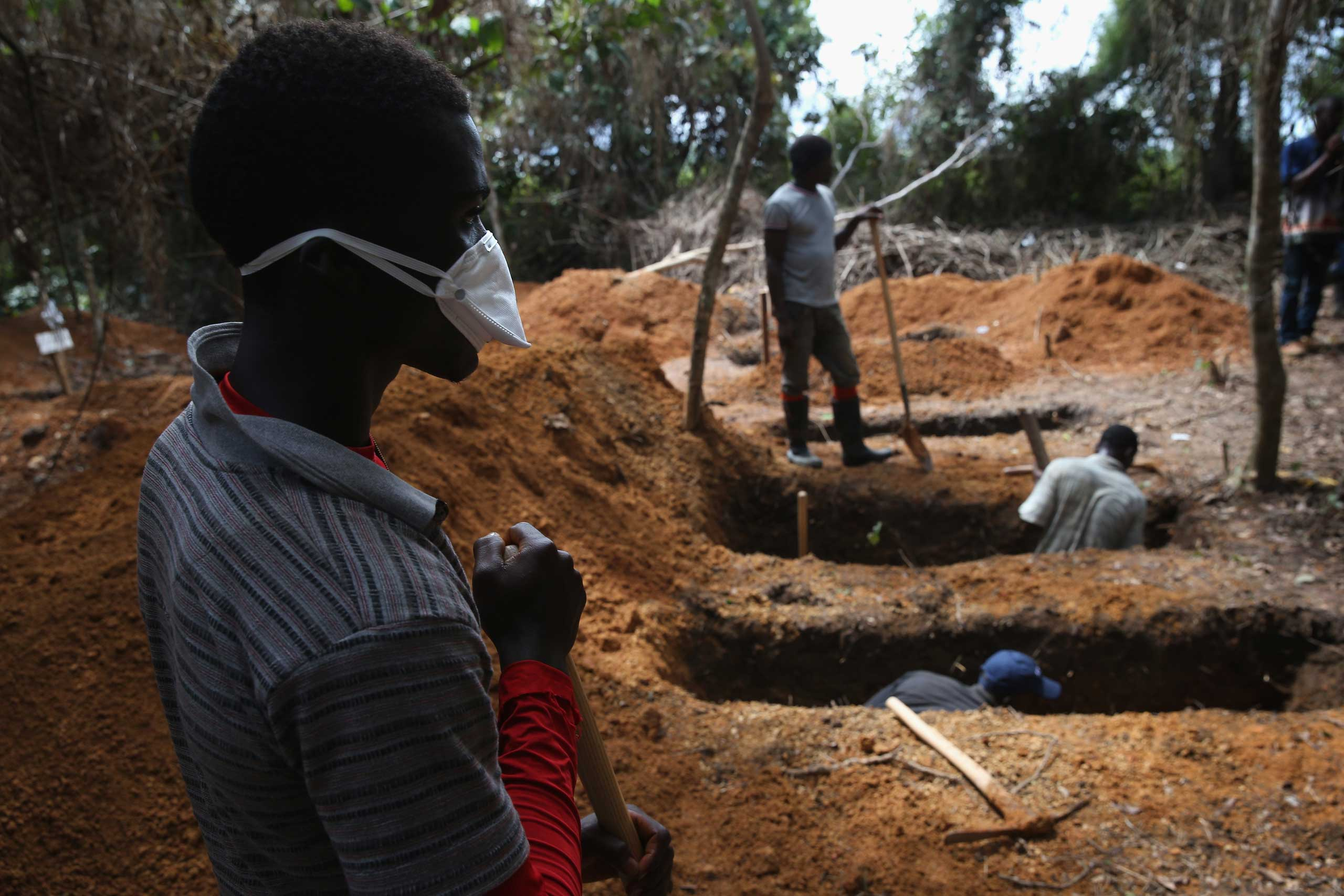 Grave diggers prepare for new Ebola victim outside an Ebola treatment center in Gbarnga, Liberia on Oct. 7, 2014.