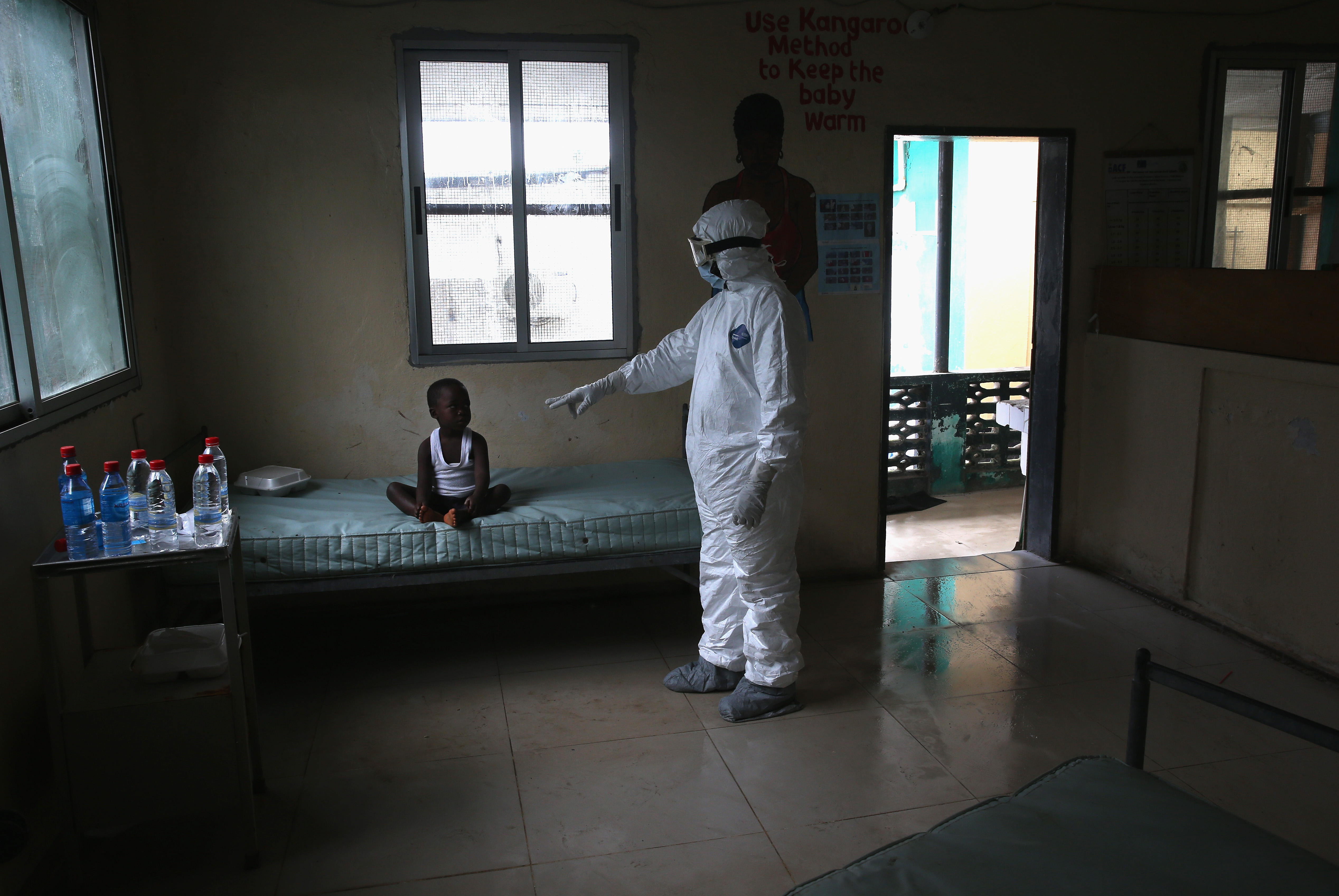 A Liberian Ministry of Health worker, dressed in an anti-contamination suit, speaks to a child in a holding center for suspected Ebola patients at Redemption Hospital on Oct. 3, 2014 in Monrovia, Liberia.