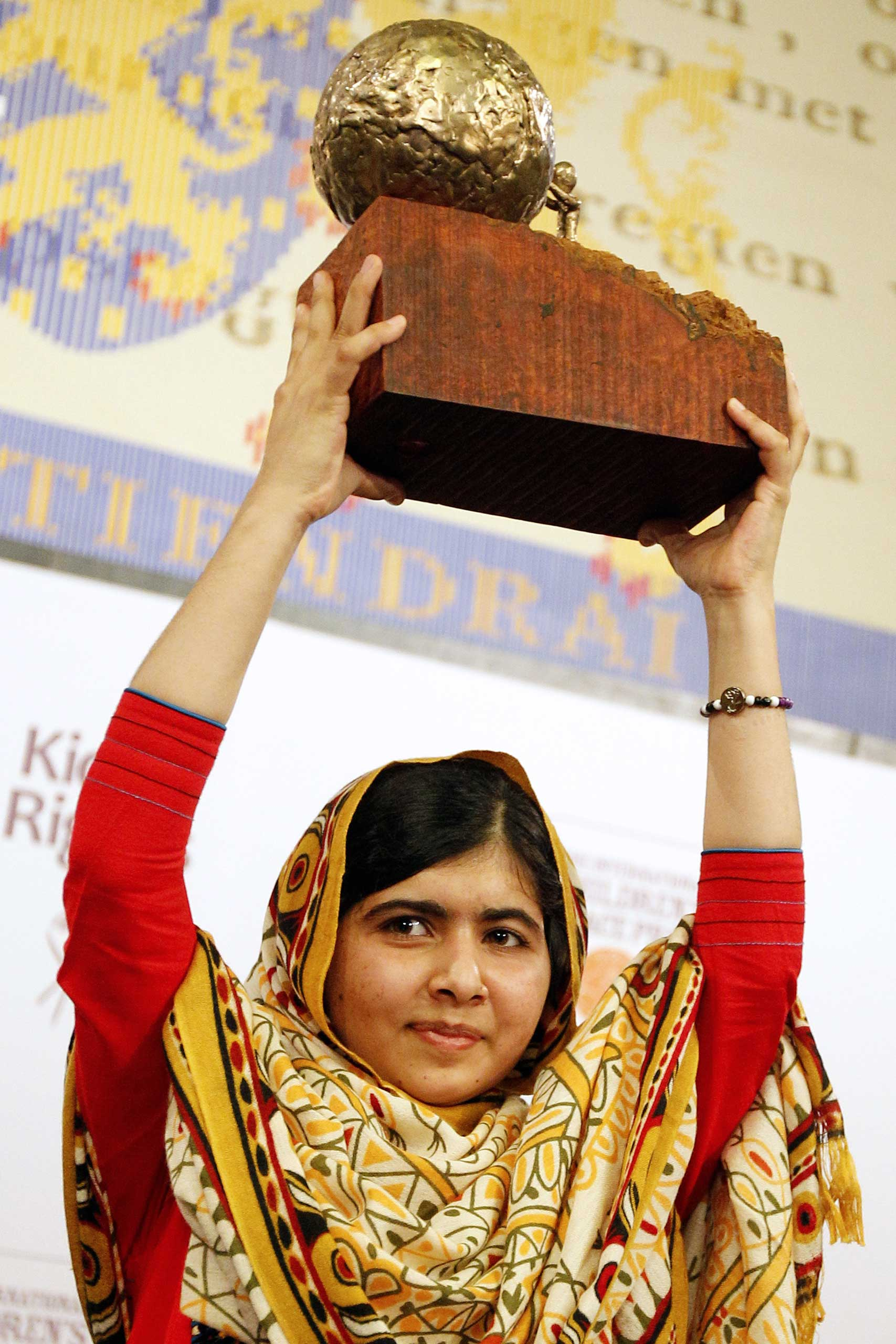 Malala Yousafzai raises a trophy after being honored with the International Children's Peace Prize in the Netherlands, on Sept. 6, 2013.