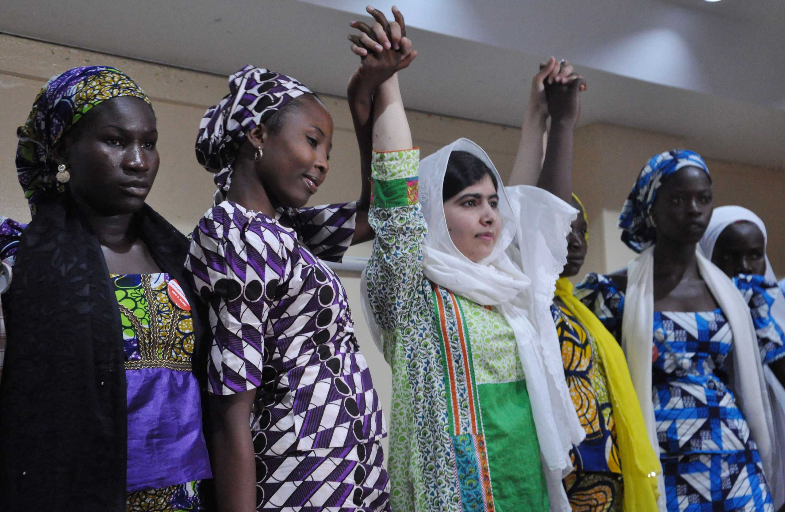 Malala Yousafzai raises her hands with some of the escaped kidnapped school girls of government secondary school Chibok during a news conference in Abuja, Nigeria on July 14, 2014.