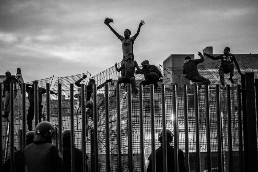 African migrants try to cross a border fence and enter the Spanish enclave of Melilla, March, 2014.