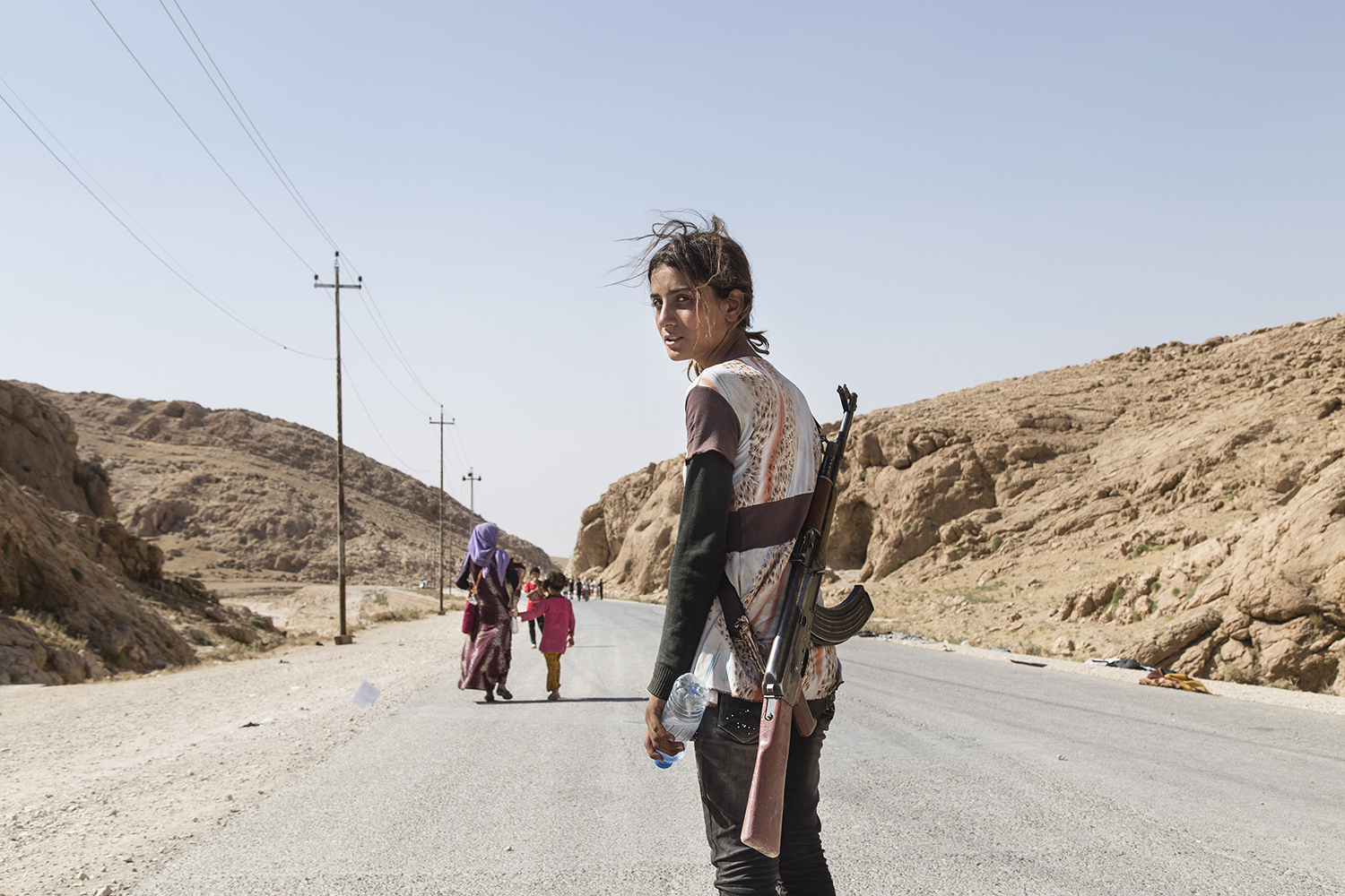 Runak,14, from Shengal, makes her way down the mountain after a week. August 2014. Sinjar Mountains, Iraq.