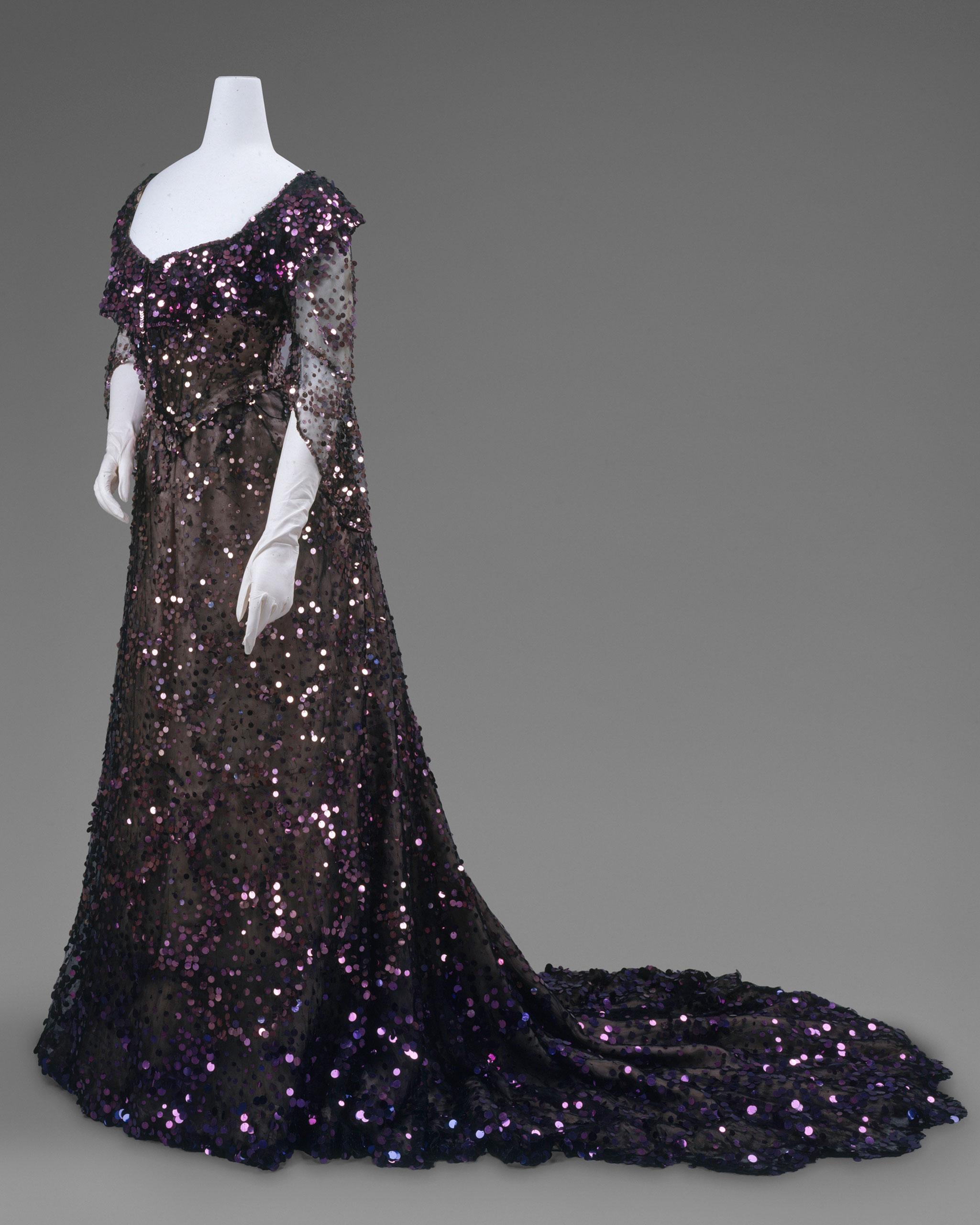 <strong>Evening Dress, 1902</strong>                                    Black silk tulle, mauve silk chiffon, purple sequins. <i>*Worn by Queen Alexandra</i>