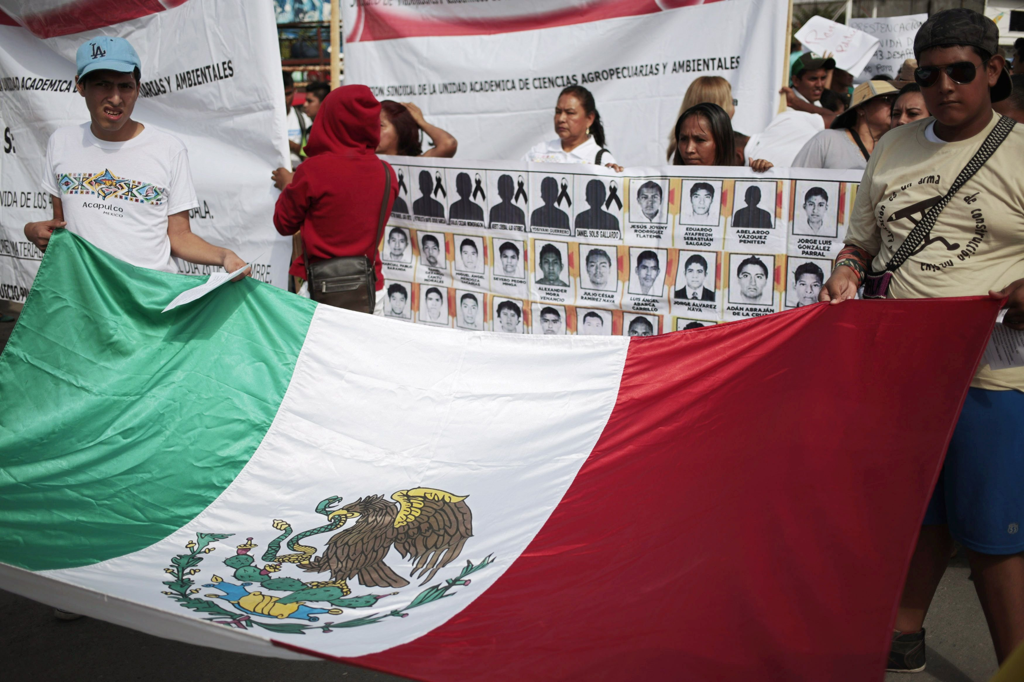 People hold a Mexican flag during a demonstration to demand information for the 43 missing students of the Ayotzinapa teachers' training college, in Iguala, the southern Mexican state of Guerrero on Oct. 22, 2014.