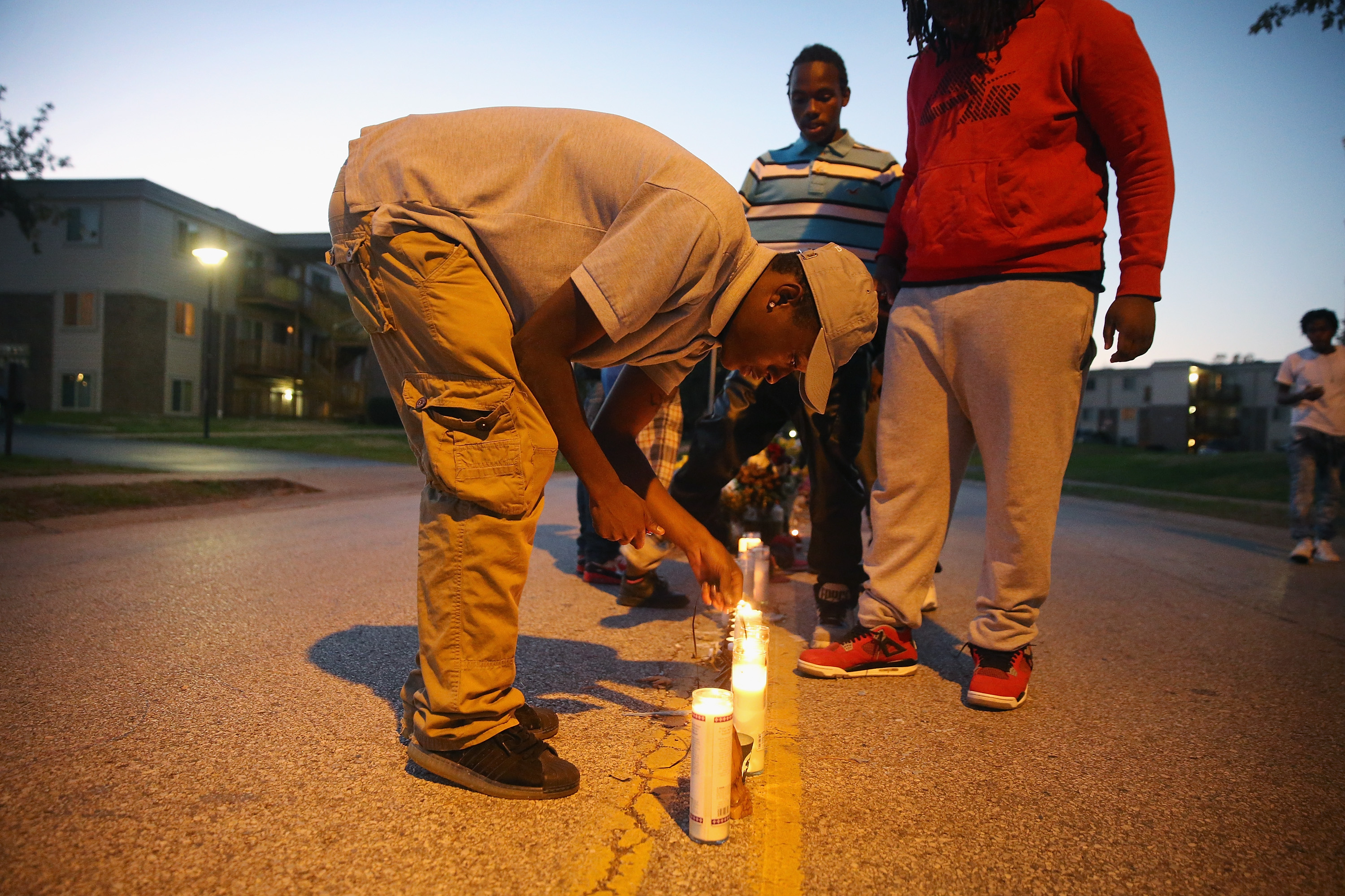 Neighborhood residents light candles at a memorial for 18-year-old Michael Brown on Canfield Street on October 20, 2014 in Ferguson, Missouri.