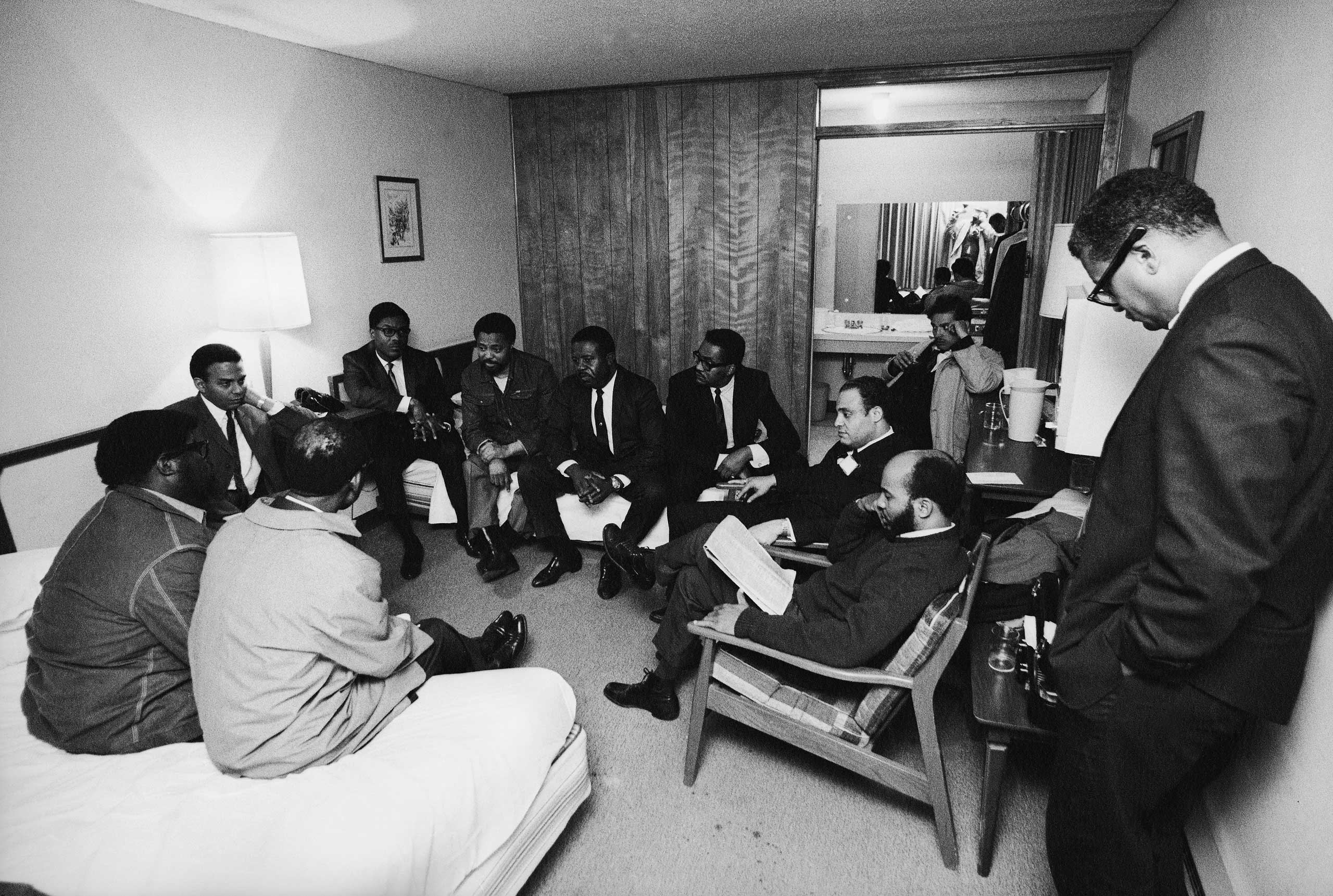 """<b>Not published in LIFE.</b> Stunned, silent members of the Southern Christian Leadership Conference in Dr. King's room at the Lorraine Motel, April 4, 1968, including Andrew Young (far left, under table lamp) and civil rights leader and Dr. King's colleague, Rev. Ralph Abernathy, in the middle on the far bed. """"I was very discreet,"""" Groskinsky recalls. """"I shot just enough to document what was going on. There, almost in the center of the picture, in the mirror, you can see my reflection. I took a couple of pictures and just kind of backed off."""""""