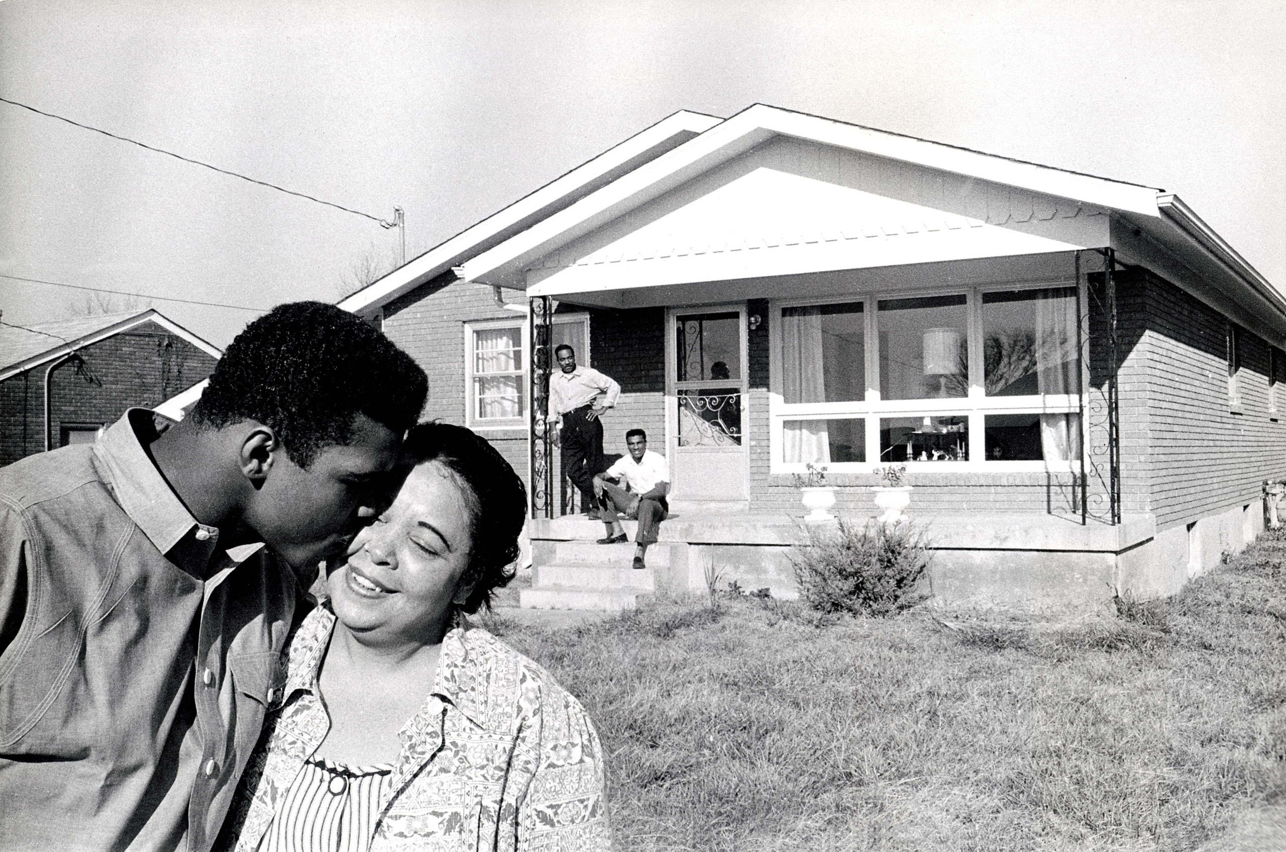 Ali is pictured with his mother, Odessa, and his Father Cassius and brother Rudolph in the background at his family home in Louisville, Ky., circa 1965.