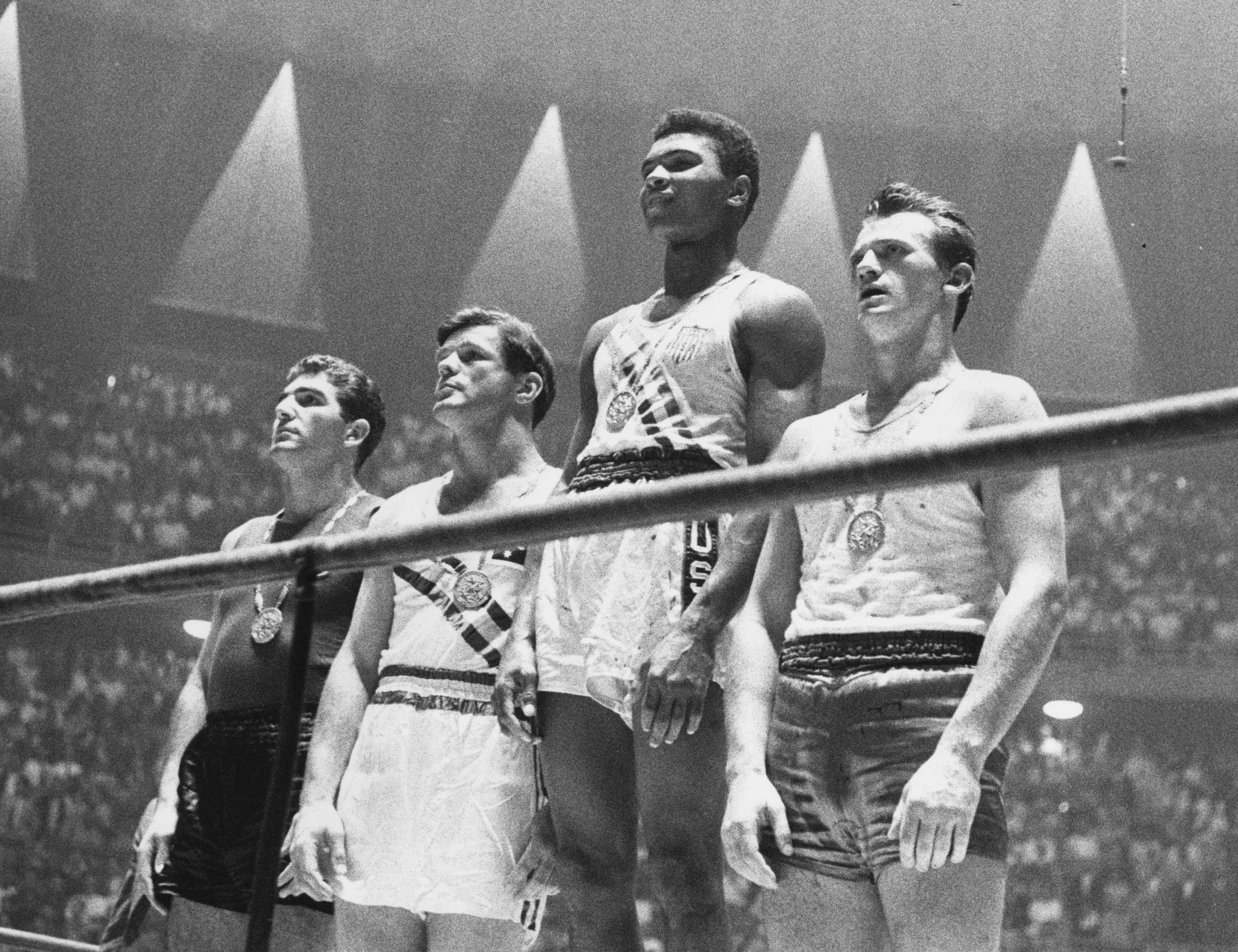 The winners of the 1960 Olympic medals for light heavyweight boxing on the winners' podium in Rome: Cassius Clay (center), gold; Zbigniew Pietrzykowski of Poland (right), silver; and Giulio Saraudi (Italy) and Anthony Madigan (Australia), joint bronze.