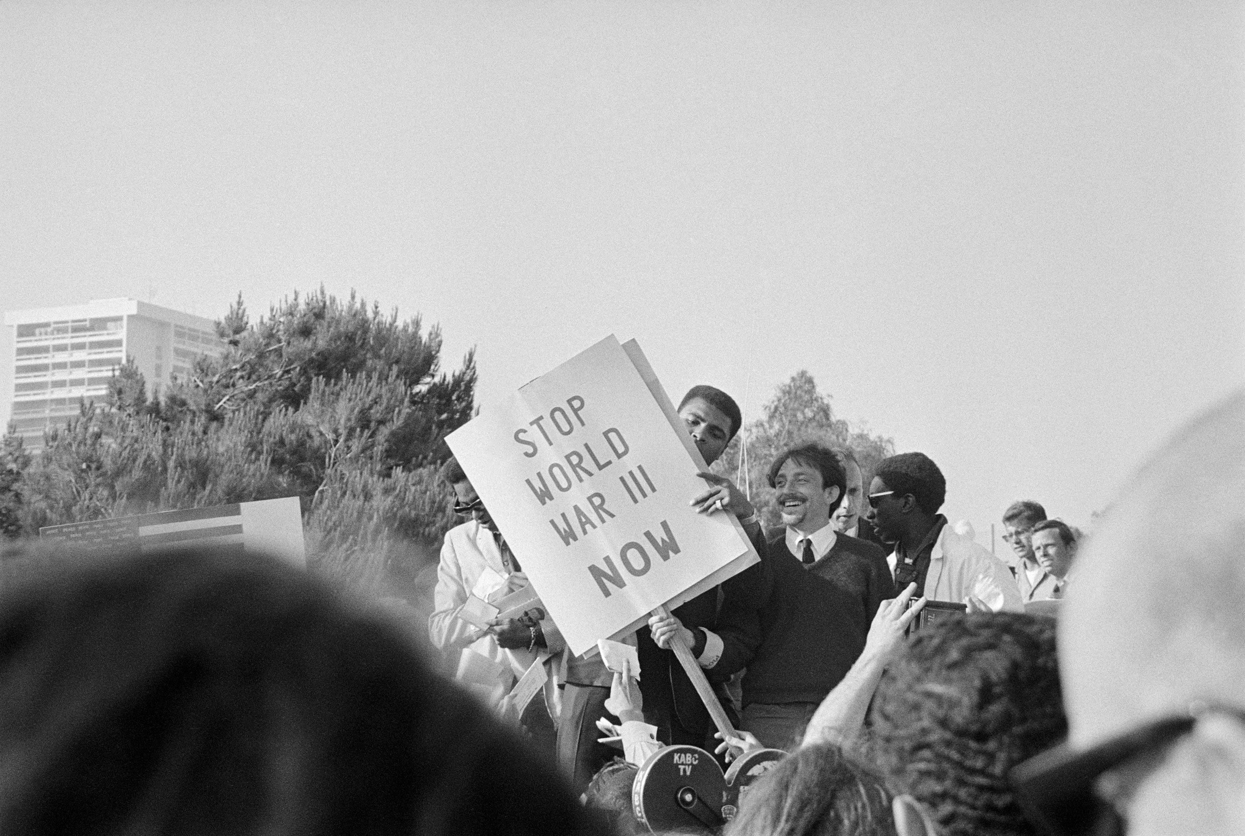 Ali peers around a 'Stop World War III' picket sign before addressing an anti-war group that had assembled to protest the Vietnam War on  June 23, 1967 in Los Angeles. The group of thousands staged a march to the Century Plaza Hotel where President Johnson was being honored which ended in a bloody battle with the police.