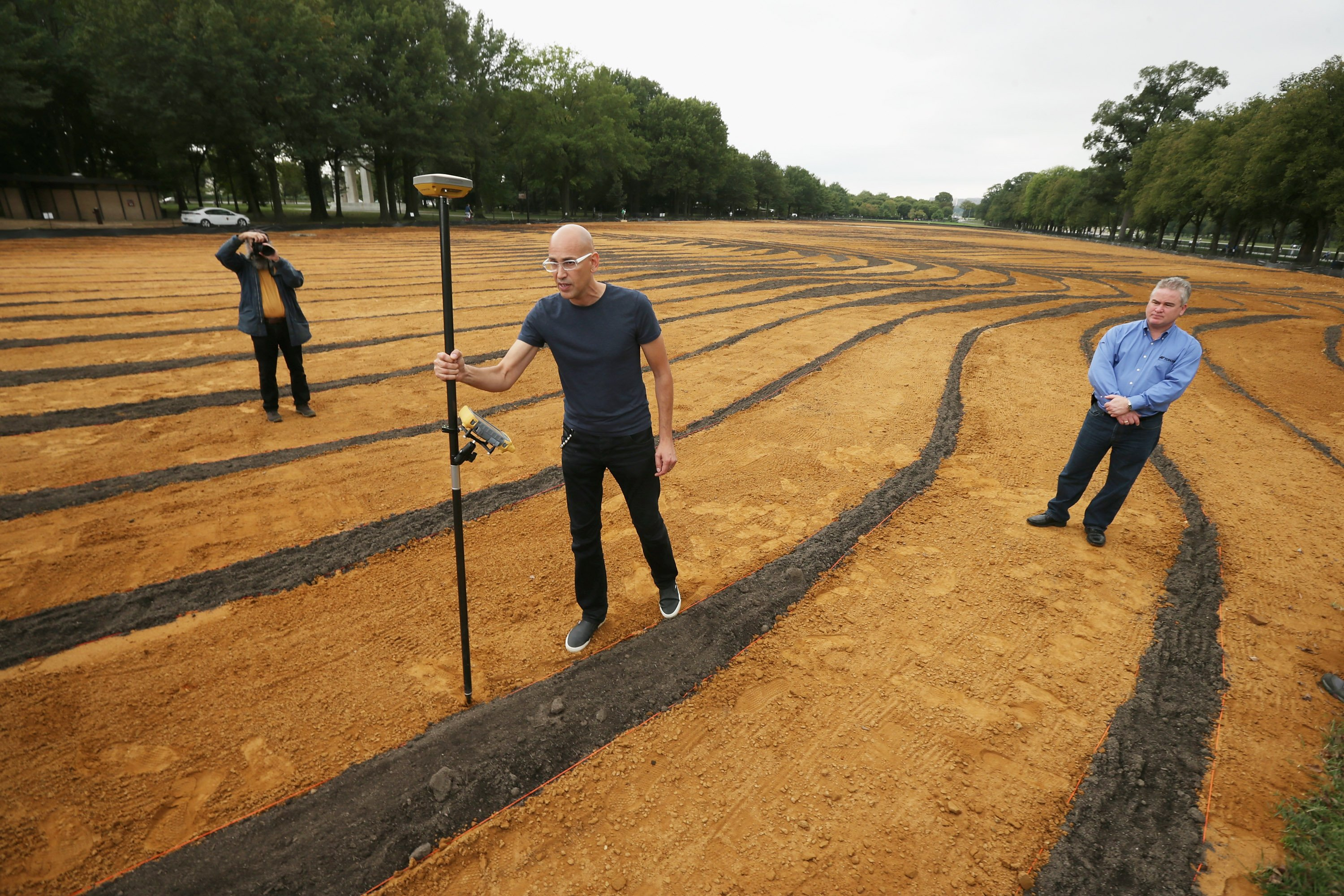 Cuban-American artist Jorge Rodriguez-Gerada demonstrates how a 'rover,' or high-precision GPS marker, was used to create his six-acre sand and soil 'facescape' on the National Mall in Washington, Oct. 1, 2014.