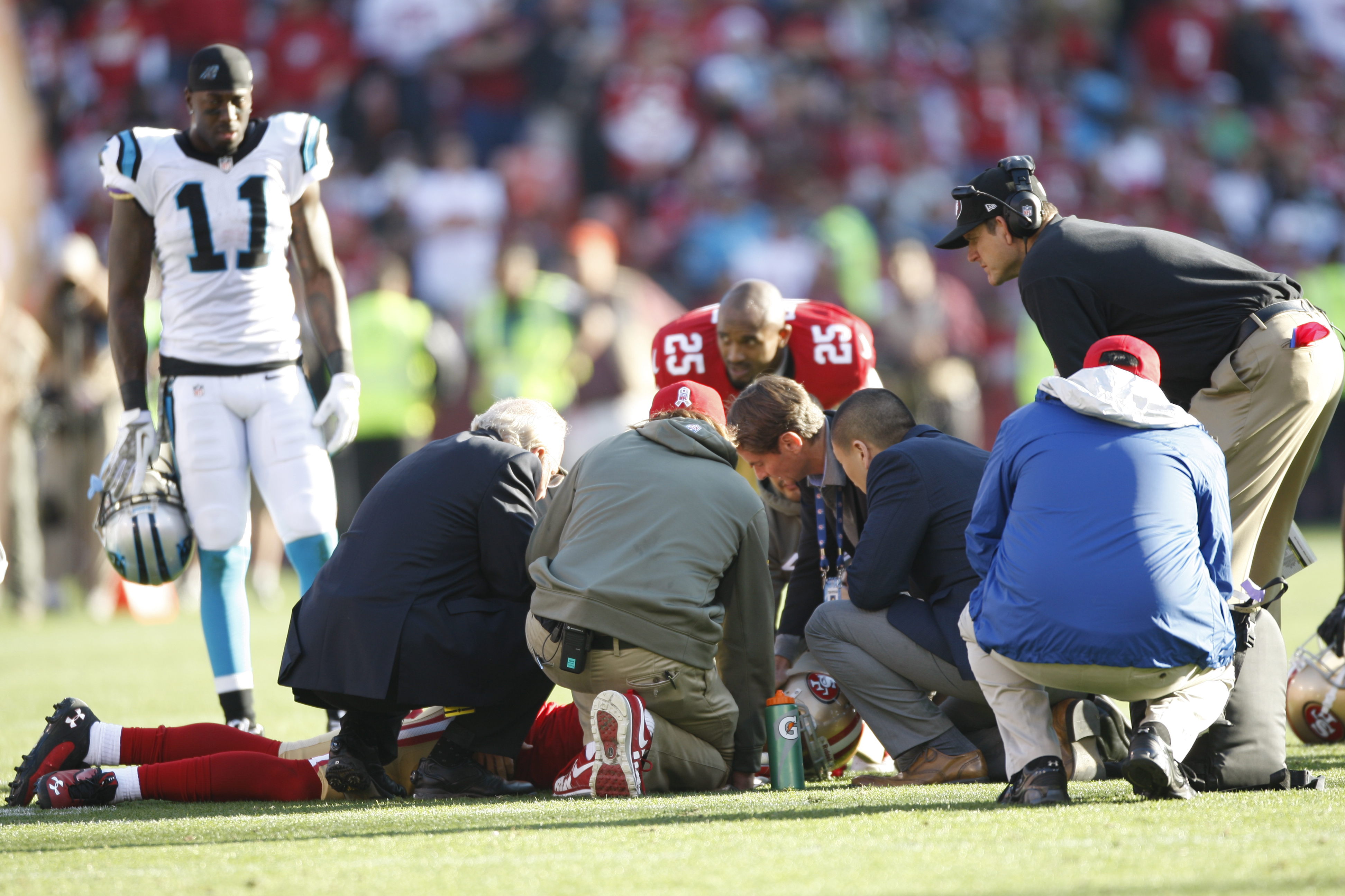 From left: Head Coach Jim Harbaugh of the San Francisco 49ers and the medical staff check out Eric Reid after he received a concussion during the game against the Carolina Panthers on November 10, 2013 in San Francisco, California.