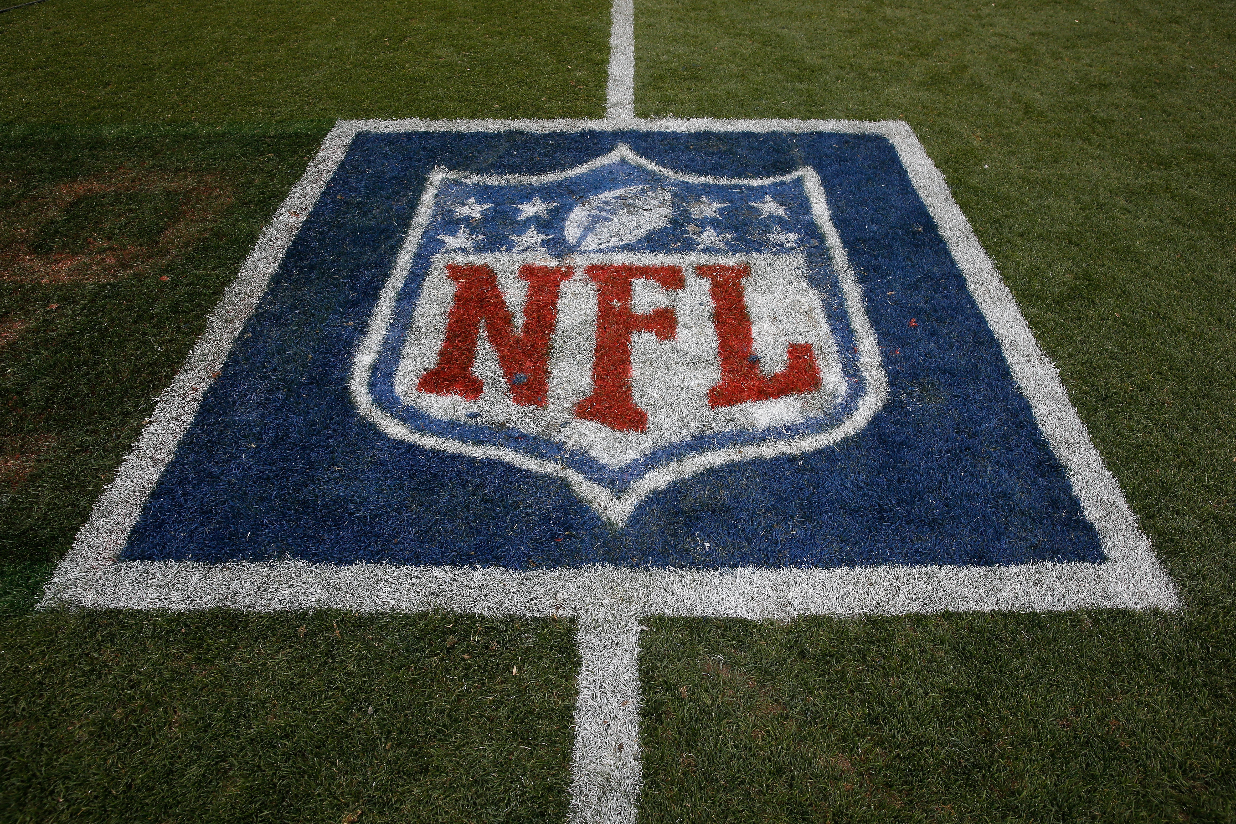 The NFL logo is displayed on the turf on September 14, 2014.