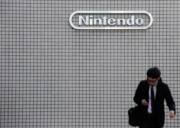 A man walks in front of a Nintendo Co. logo outside the company's offices in Tokyo, Japan.