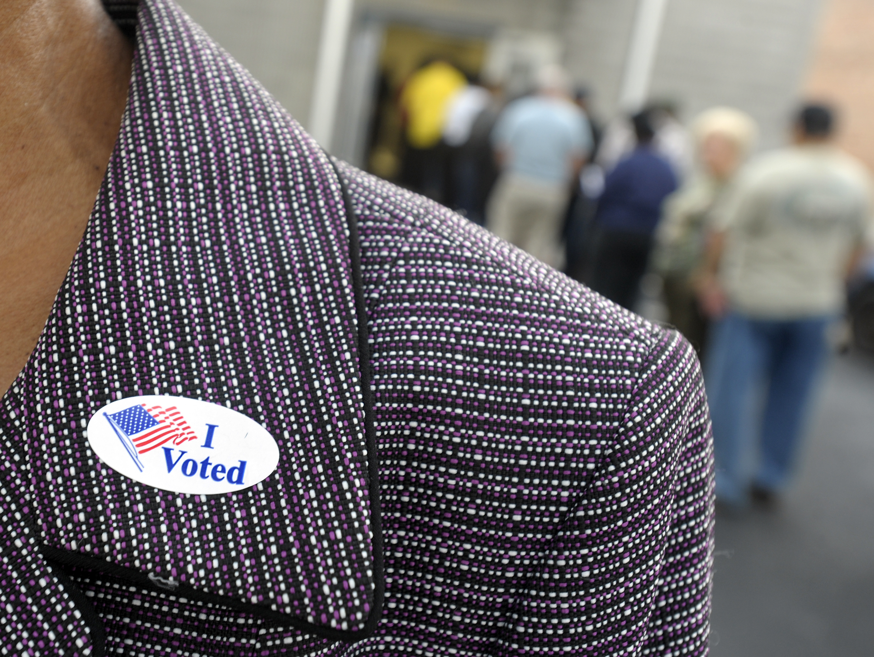 A voter displays an  I Voted  sticker on her lapel after voting as others wait in line for the first day of early voting on Oct. 18, 2012, in Wilson, N.C.