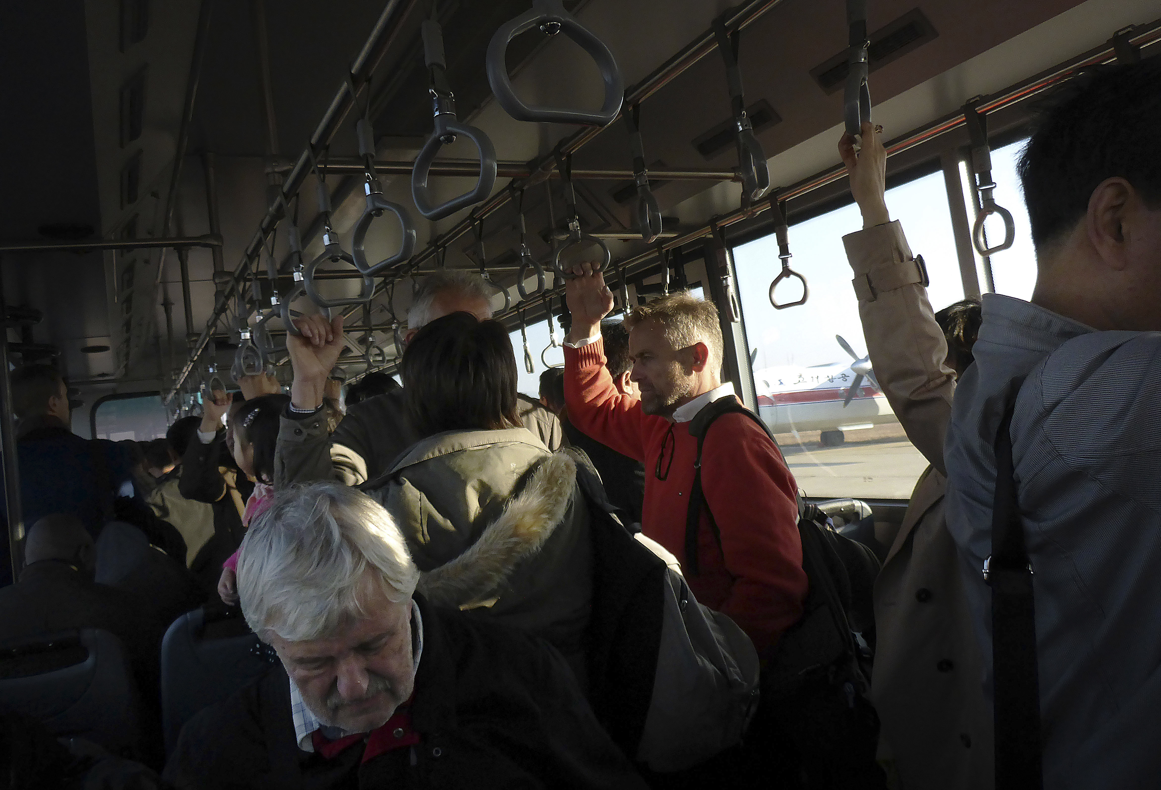 This Oct. 28, 2014, photo shows foreigners and North Koreans riding a shuttle bus to a plane bound for Beijing at the Sunan International Airport, in Pyongyang