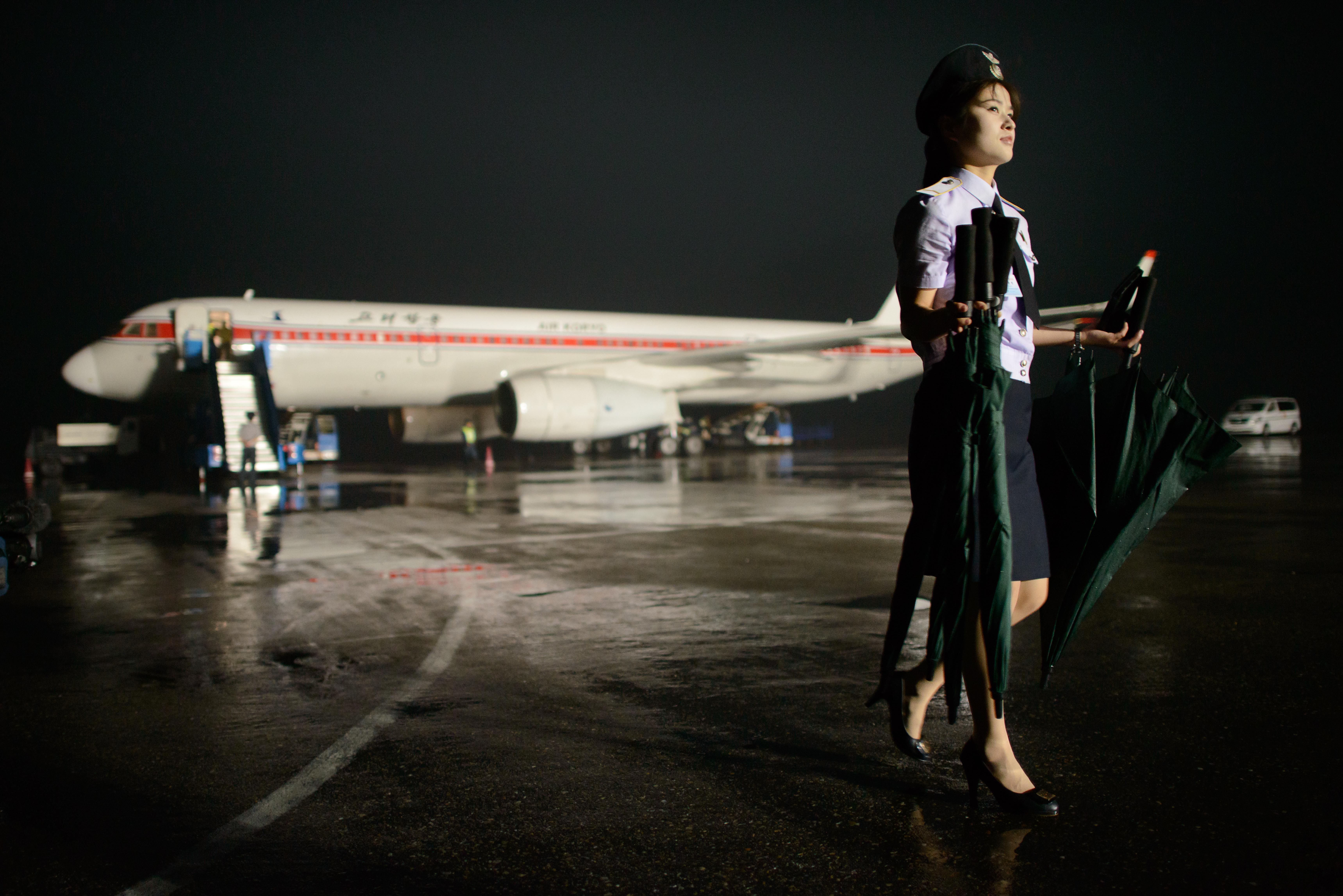 In a photo taken on July 24, 2013 a North Korean airport staff member carries umbrellas before an Air Koryo aircraft in Pyongyang.