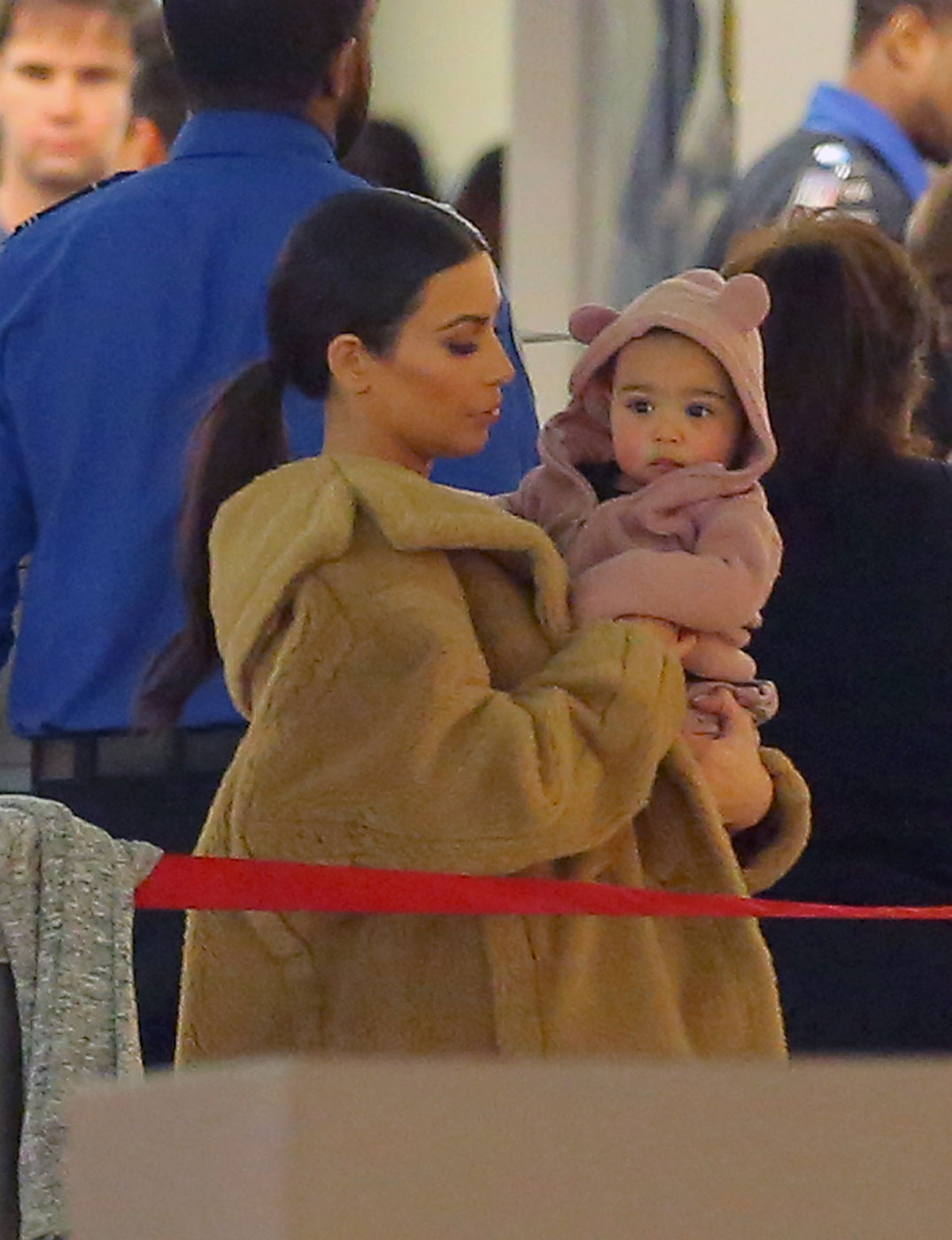 Kim Kardashian holds baby North West while wearing a fur coat inside JFK airport in New York City on Feb. 26, 2104.