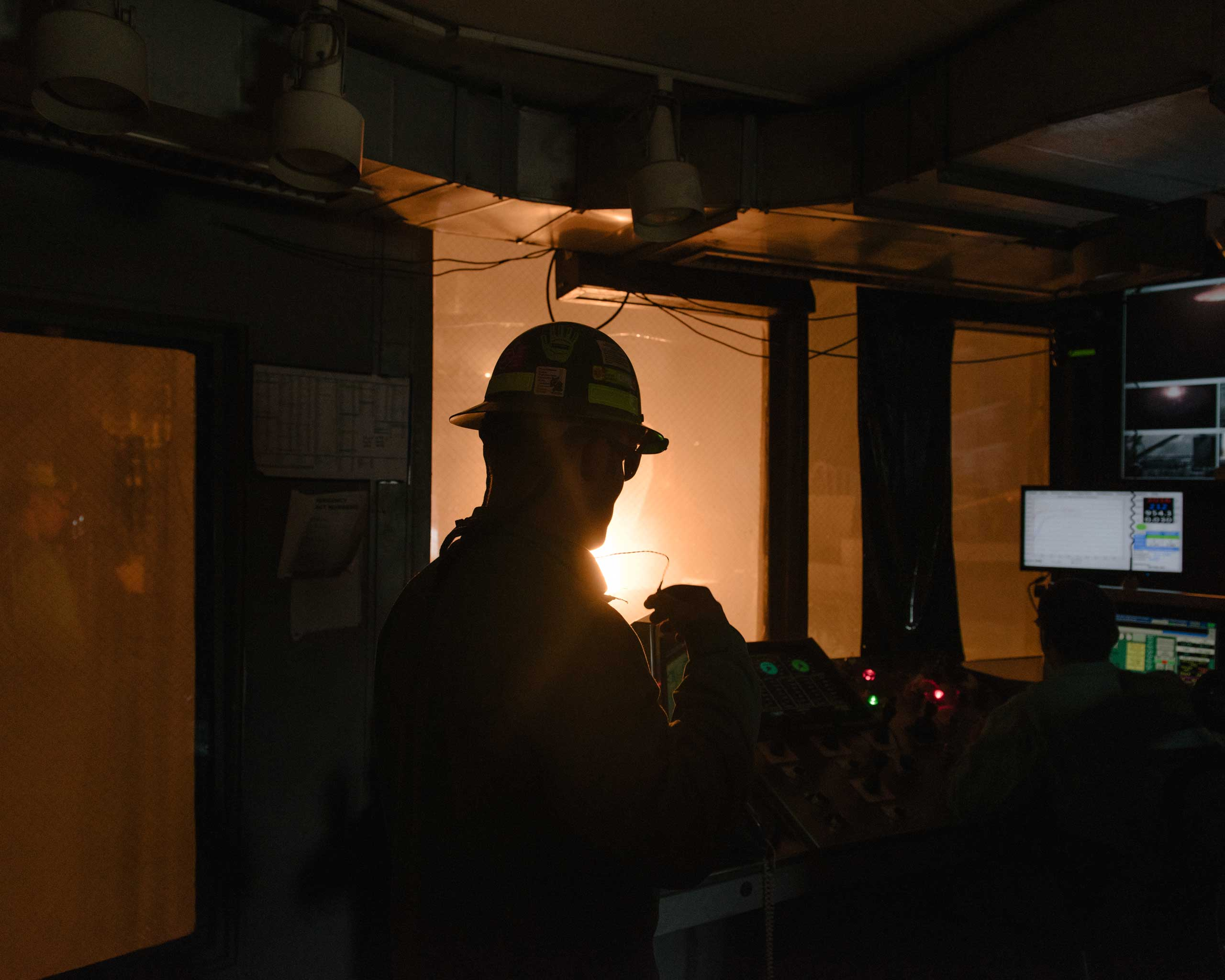 A Nucor steelworker monitors the furnace from inside a control room in the mill's melt shop, where scrap is liquified, Crawfordsville, Ind. on Aug. 25, 2014.