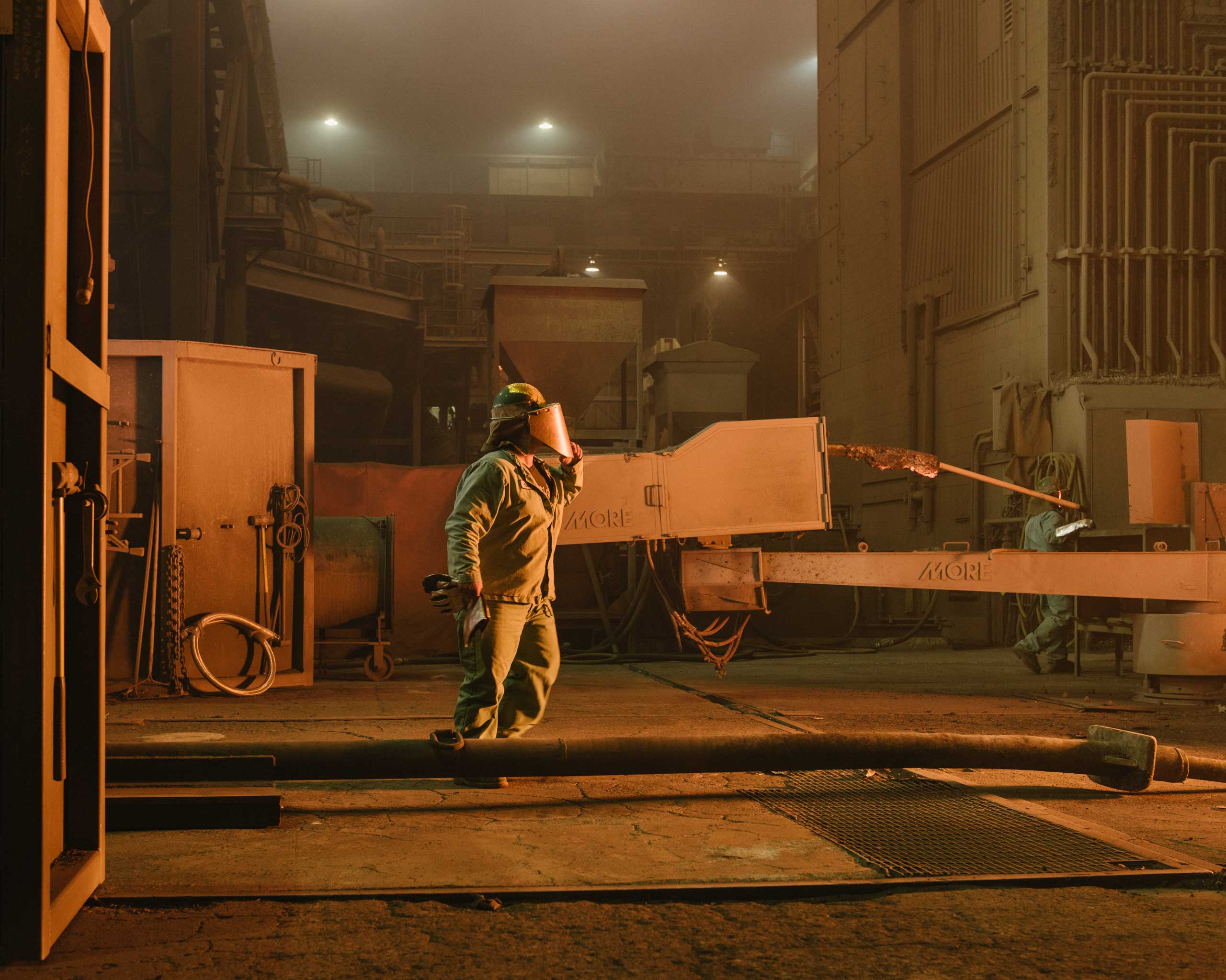 A worker approaches the electric-arc furnace, which uses three giant                     electrodes to melt scrap into molten steel. Nucor's workers are among the                     highest-paid in the industry, Crawfordsville, Ind. on Aug. 25, 2014.