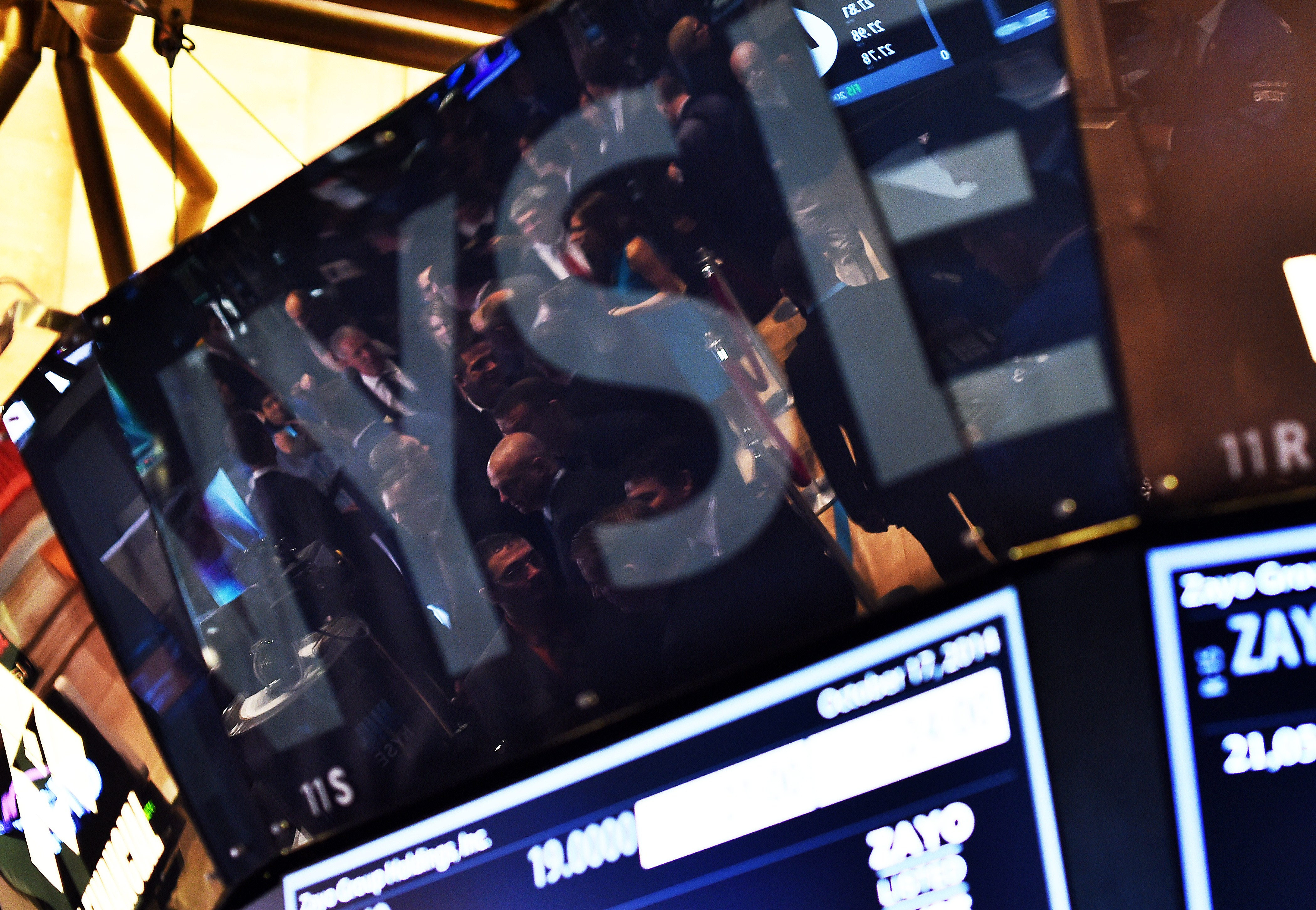 Traders are seen reflected on an electronic display as they work on the floor of the New York Stock Exchange on October 17, 2014 in New York.