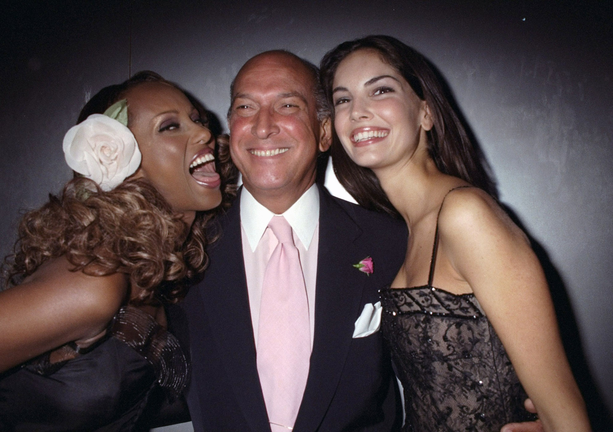 Oscar de la Renta is flanked by models Iman (left) and Eugenia at a party at the Copacabana to launch his new perfume in September 1997.