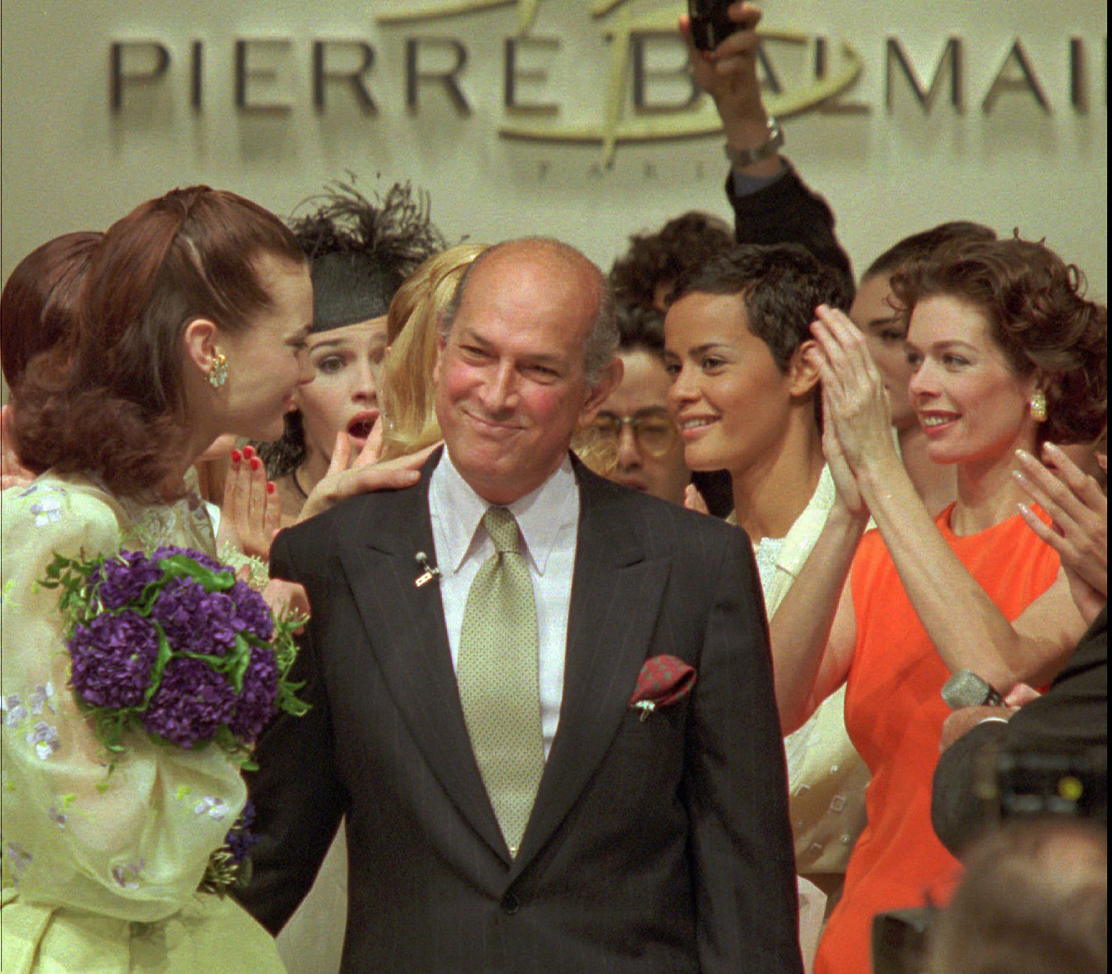 Oscar de la Renta is cheered by models at the end of the Pierre Balmain 1996 Spring-Summer haute couture show in Paris on Jan 24, 1996.