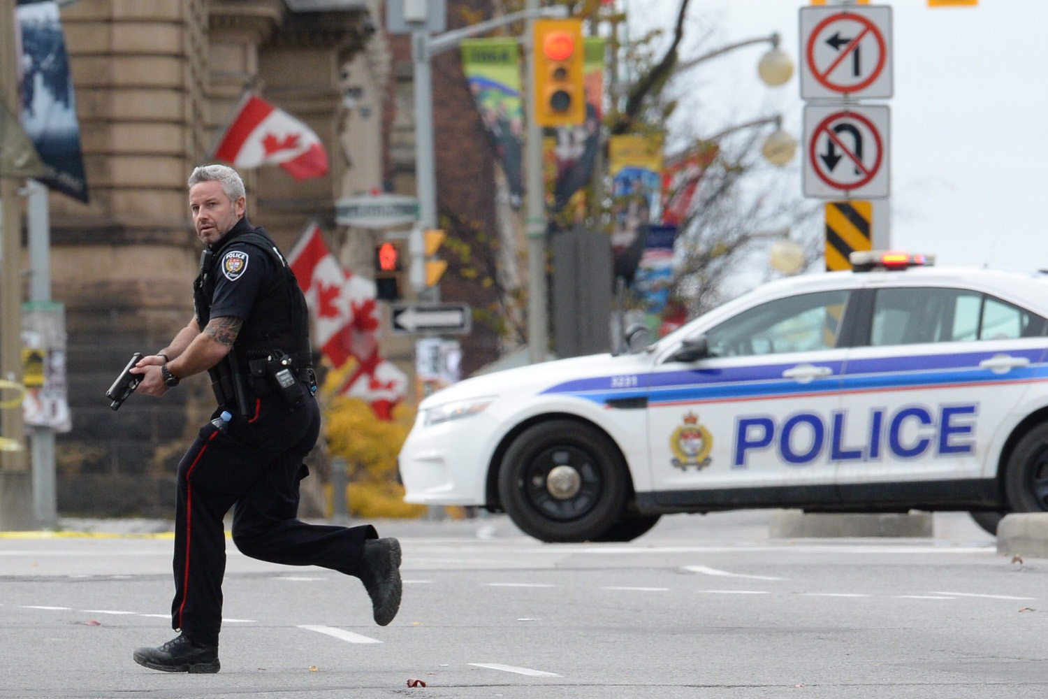 An Ottawa police officer runs with his weapon drawn outside Parliament Hill in Ottawa on Oct. 22, 2014.