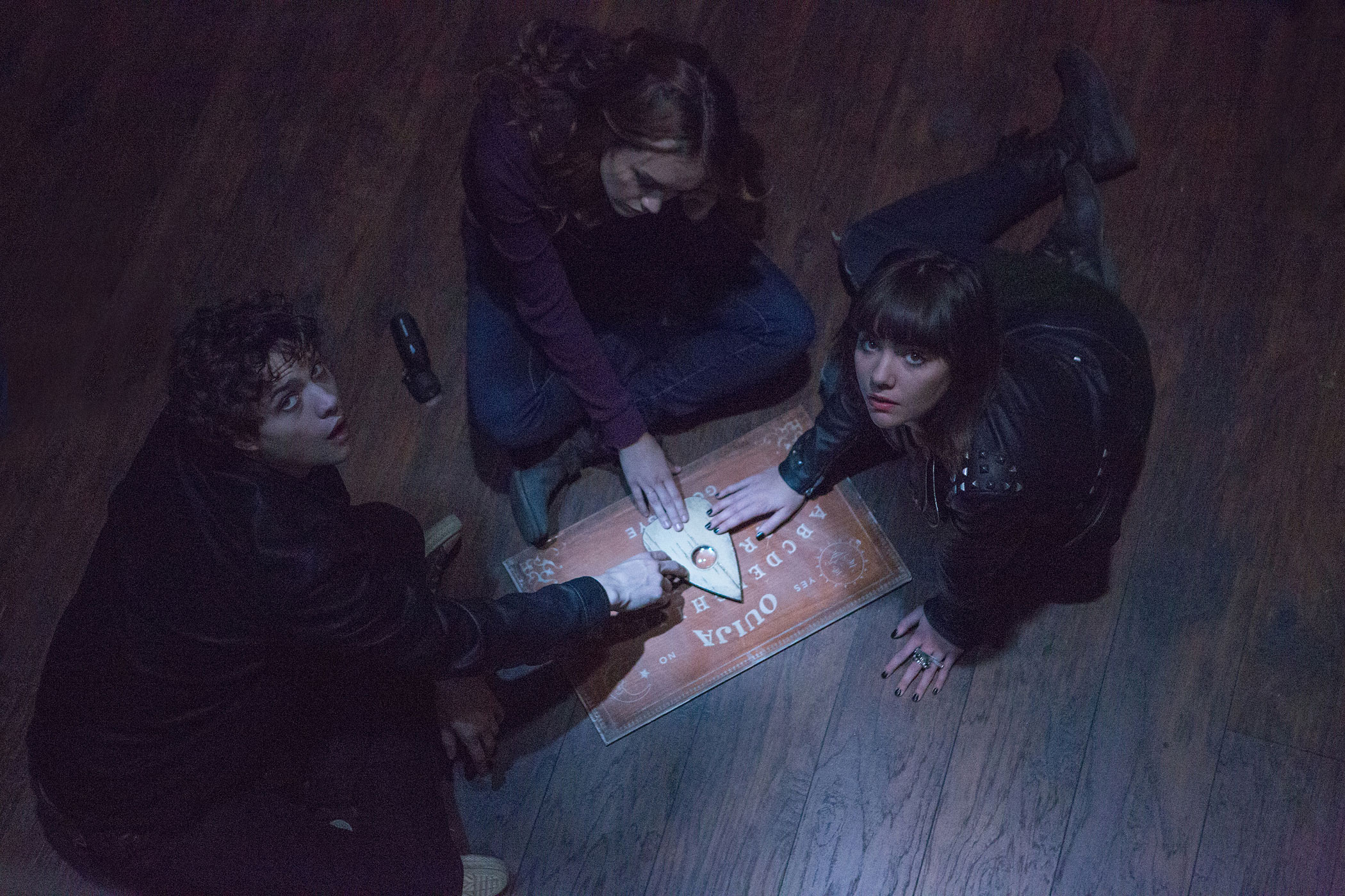 (L to R) Pete (DOUGLAS SMITH), Laine (OLIVIA COOKE) and Sarah (ANA COTO) play the game in  Ouija , a supernatural thriller about a group of friends who must confront their most terrifying fears when they awaken the dark powers of an ancient spirit board.