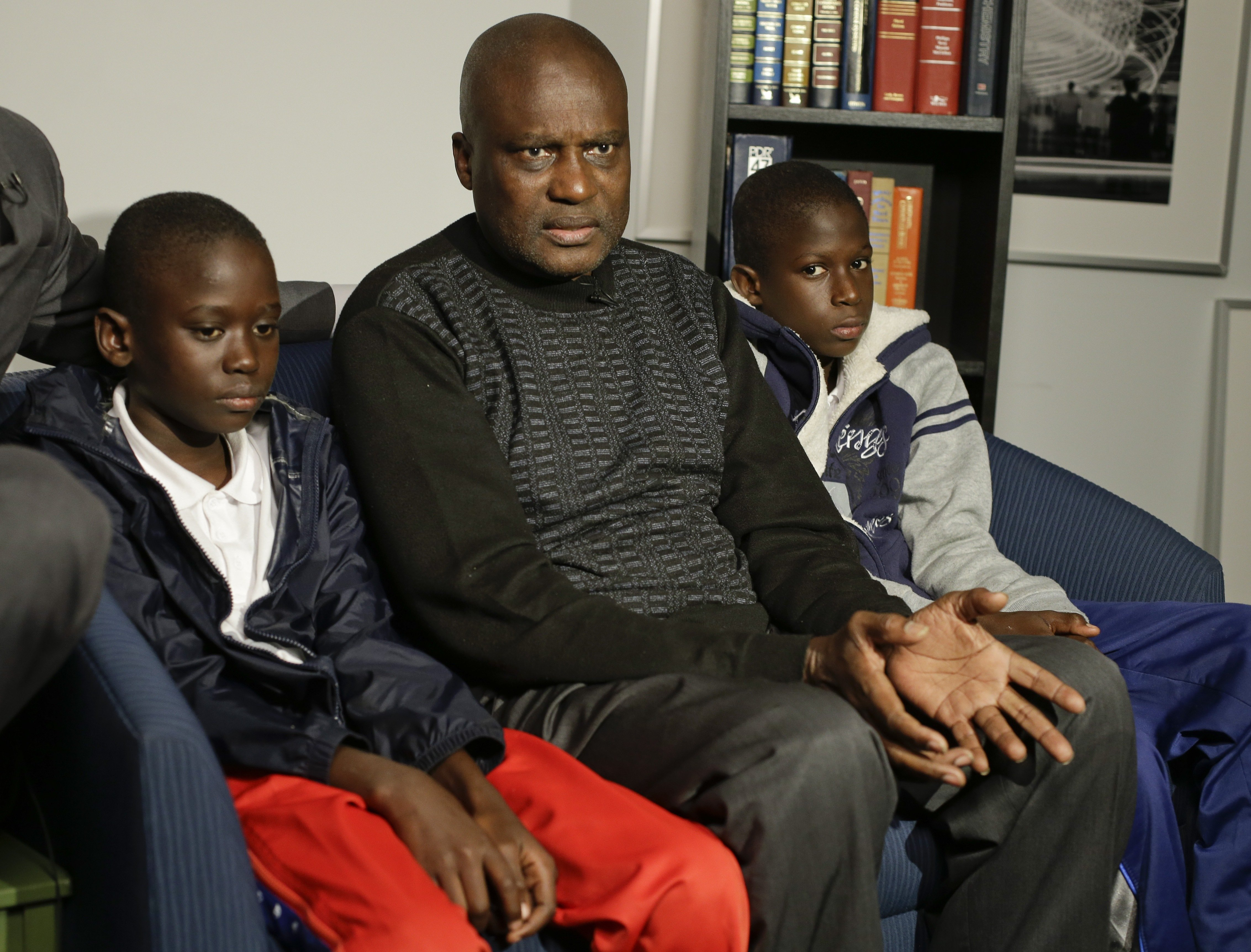 Amadou Drame, left, 11, and brother Pape Drame, right, 13, listen as their father Ousmane Drame responds to questions during a news interview on Oct. 28, 2014, in New York City