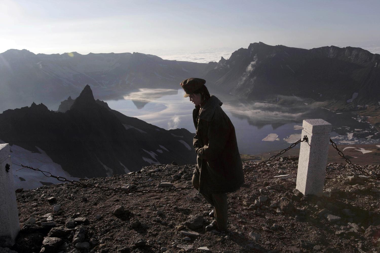A North Korean woman walks on the peak of Mt. Paektu in North Korea's Ryanggang province, June 18, 2014 .