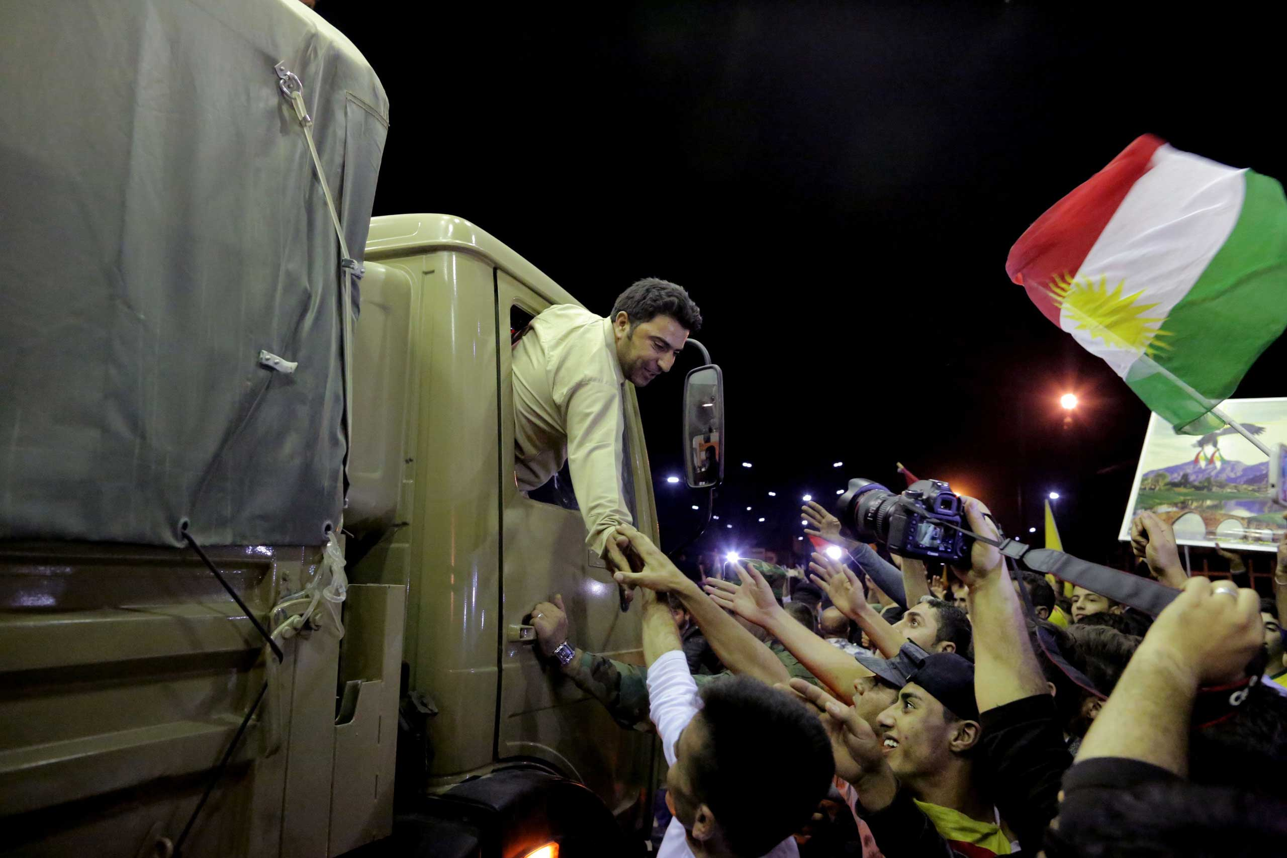 A Kurdish Peshmerga soldier reaches out his hand to supporters, at the Ibrahim Khalil border crossing, in the Northern Kurdish Region of Iraq,  Oct. 29, 2014.