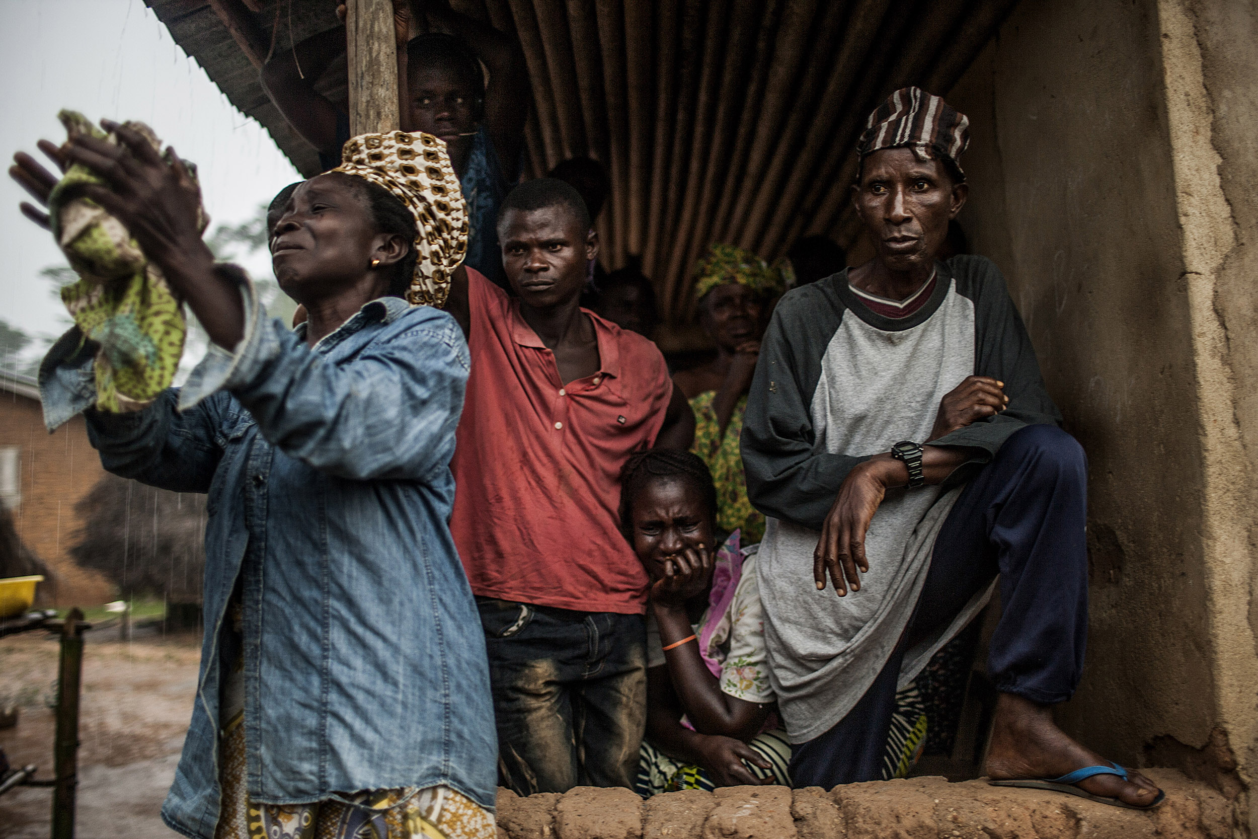 """<b>Pete Muller, Aug. 26, 2014. Sengema, Sierra Leone.</b>""""The rain started shortly after a small team of Red Cross burial workers approached the body. The deceased man, reportedly in his mid-sixties, collapsed and died outside his remote home more than a day before the burial team arrived. Having received instructions from officials that bodies of Ebola victims are extremely contagious, his family members placed a sheet over his body, marked a cordon in the sand, and called the Red Cross. With approximately 20 burial workers serving all of Kailahun district, an area the size of Rhode Island and rife with Ebola, the team had a backlog of cases. His family endured the presence of his body, laying prone and exposed to the elements, for more than 24 hours. As the team removed the sheet, the stench of death filled the air. The white cloth around the man's head was crimson with blood. As burial workers sprayed him with chlorine, family members erupted with emotion. I was moved imagining how I might respond if I were in the situation. To me, this picture represents the range of Ebola's emotional impact. In the two women, we see the devastation and loss that the virus causes. In the faces of the men, we see a sense of despondence, disbelief and suspicion that also defines the response. It was a difficult but necessary picture to make."""""""