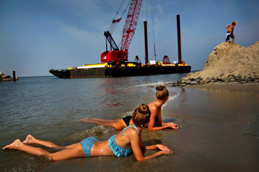 People enjoy the beach next to some heavy equipment in place for jetty construction on Willoughby Spit in Ocean View in Norfolk, Virginia. 2013.