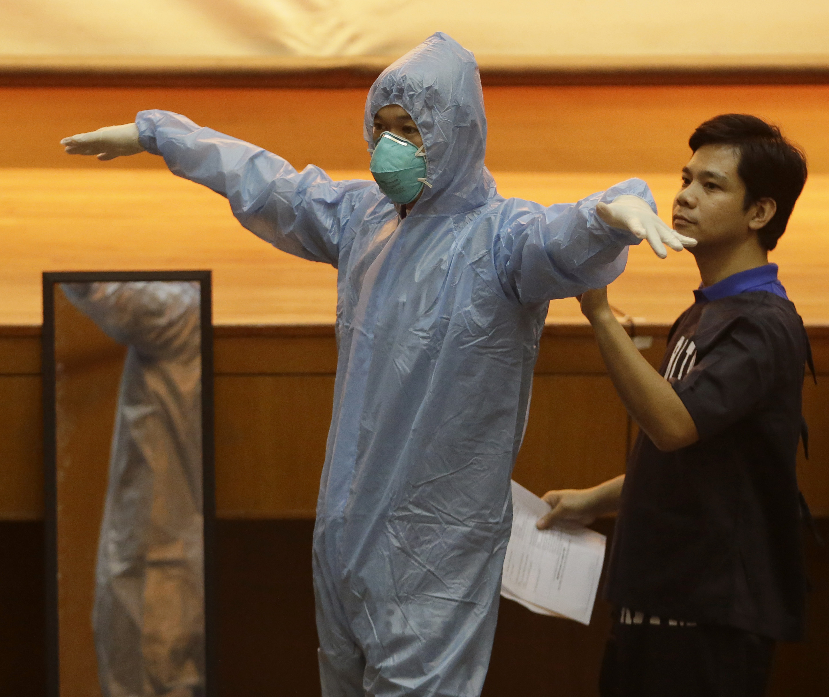 Government health workers practice wearing Ebola protective suits on the first day of training on hospital management for Ebola virus at the Research Institute for Tropical Medicine in the Philippine city of Muntinlupa on Oct. 28, 2014