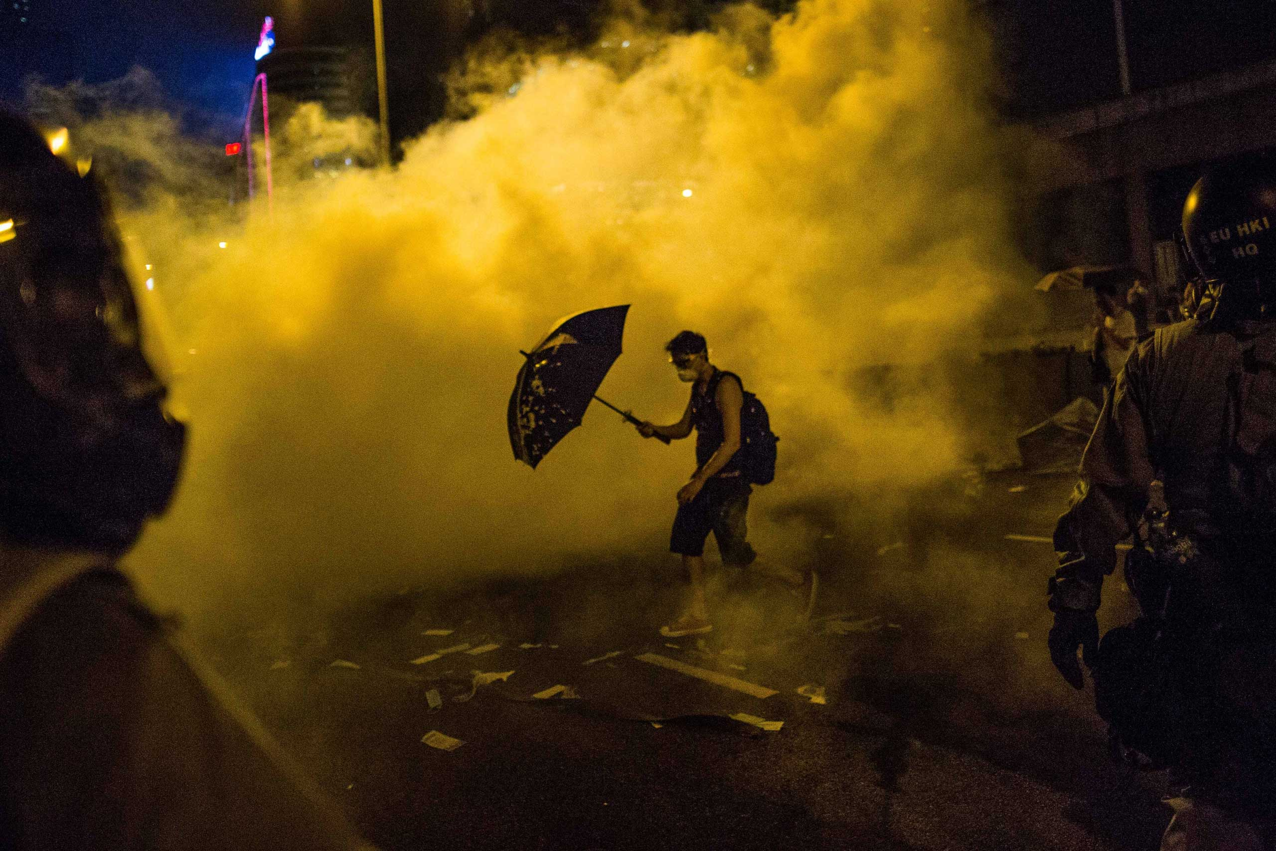 September 28, 2014 - Hong Kong, China: A solitary demonstrator eases through clouds of tear gas holding his umbrella for protection outside Government Headquarters as he's surrounded by riot police. (Todd Darling/Polaris)