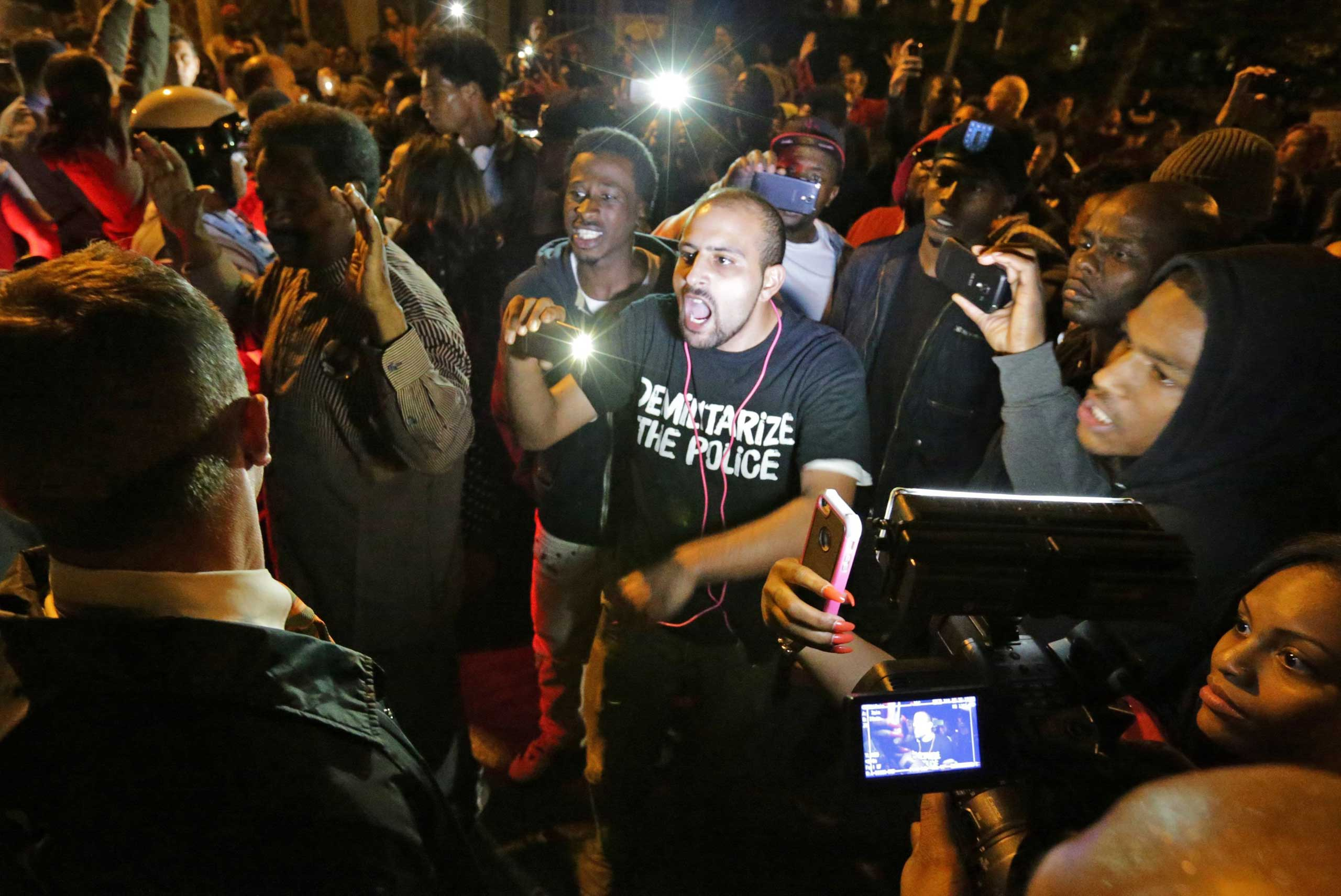 Crowds confront police near the scene in south St. Louis where a man was fatally shot by an off-duty St. Louis police officer on Oct. 8, 2014.
