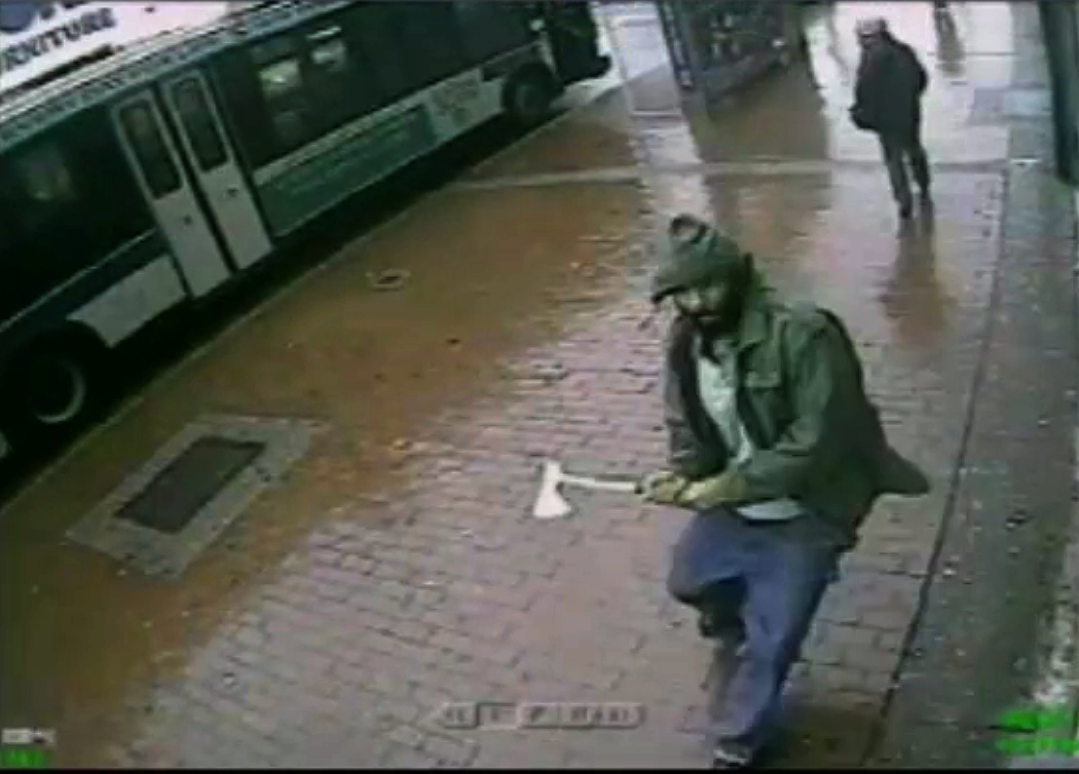In this frame grab taken from video provided by the New York Police Department, an unidentified man approaches New York City police officers with a hatchet, Thursday, Oct. 23, 2014, in the Queens borough of New York.