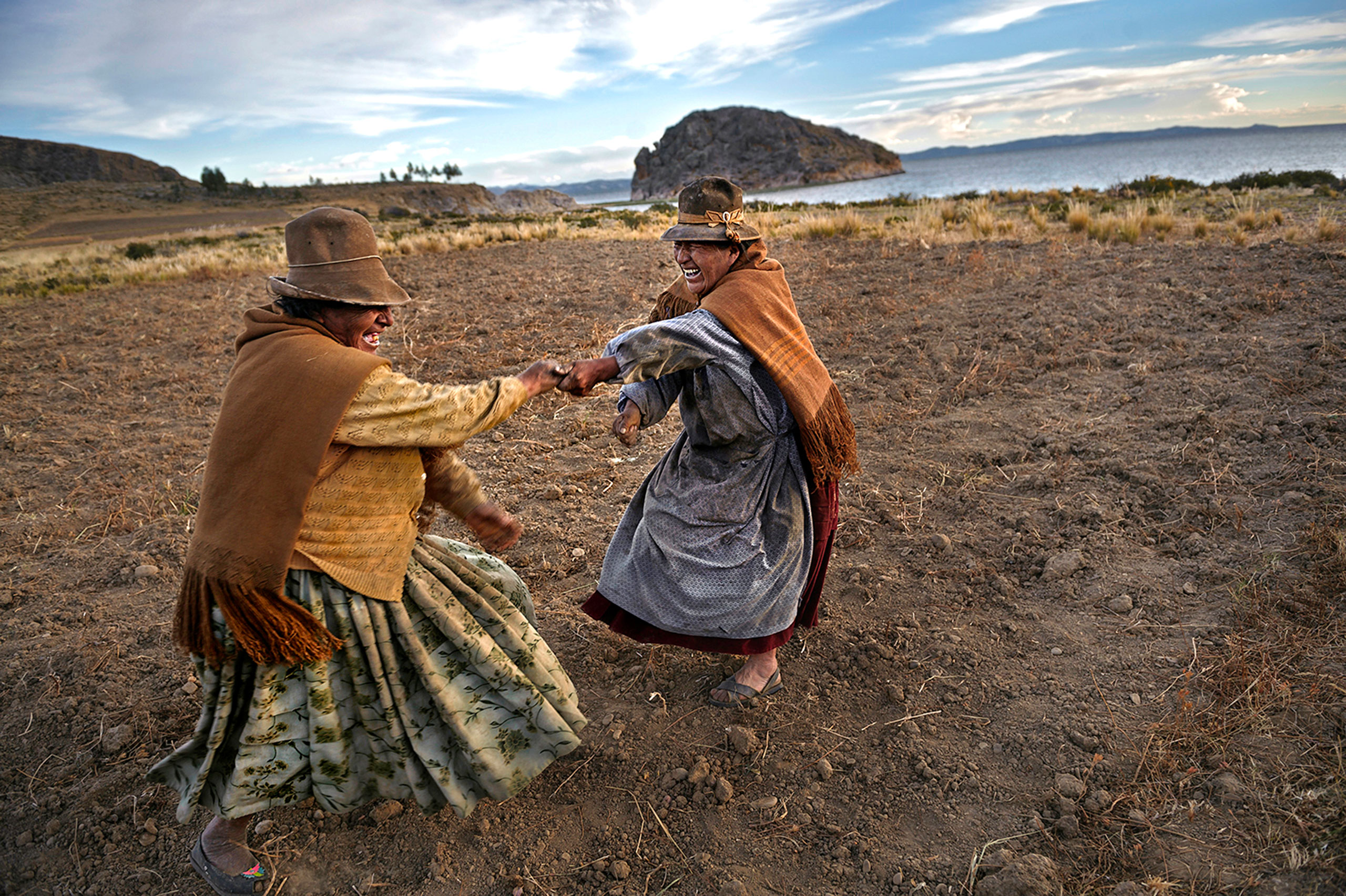 Dominga Illari, 70, left, and Manuela Quispe Avile, 70, right, dance after harvesting potatoes. Avile is the owner of the land and Illari works for her in exchange for food to eat, not money in Santiago de Okola, Bolivia.
