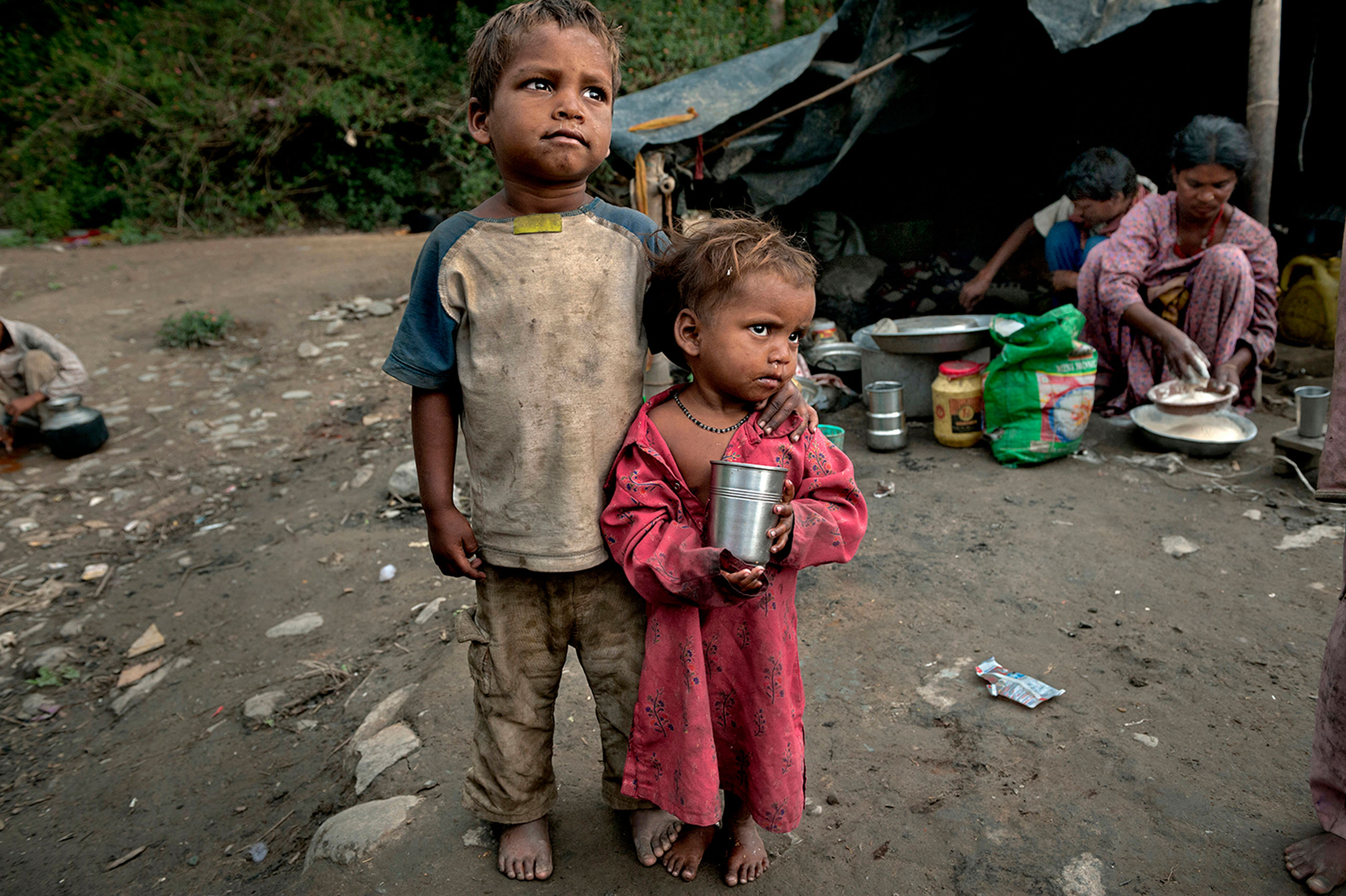 Rudra, 5, and his sister Suhani, 3, search for tea to drink at the Charan slum Settlement in Dharamsala, India, where they live with their family. They survive although two of their siblings recently died of malnutrition.