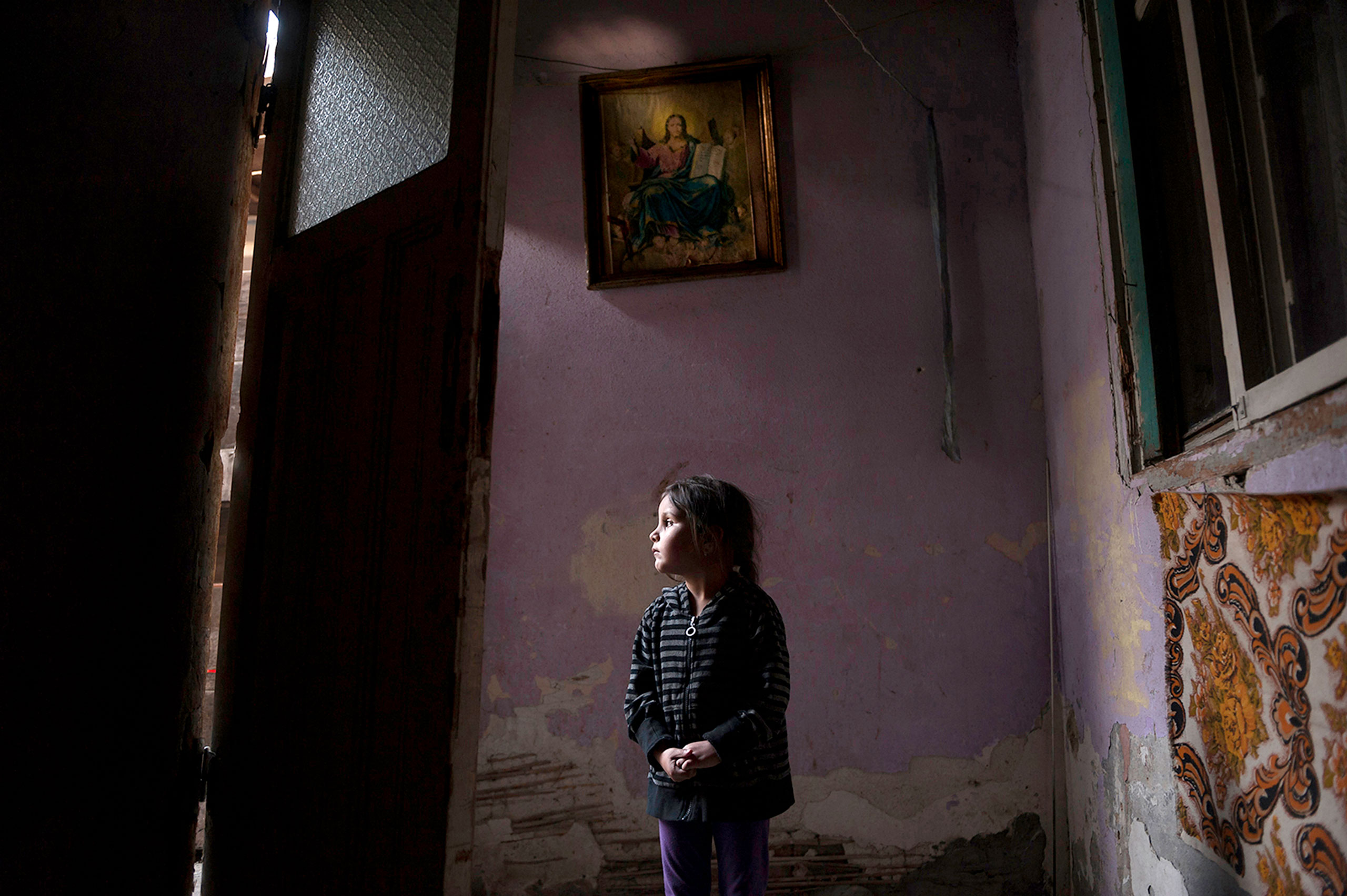 Four-year-old Ana-Maria Tudor, above, stands in the light of her doorway in Bucharest, Romania, hoping for a miracle as her family faces eviction from the only home they have ever had. Her father recently had a gall bladder surgery that resulted in an infection and left him unable to work. The one room they live in has no bathroom or running water.